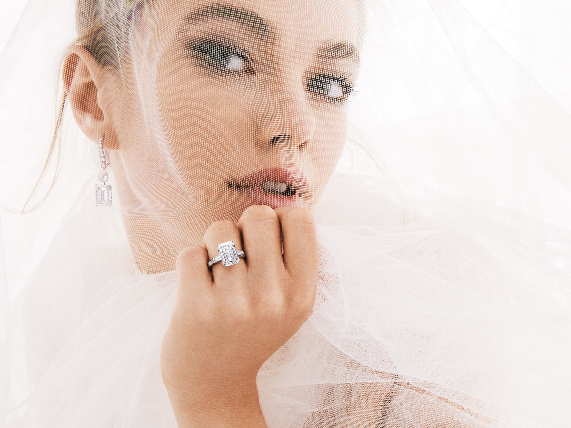 Bridal model wears Classic Graff solitaire earrings and Graff Promise Emerald Cut Engagement Ring