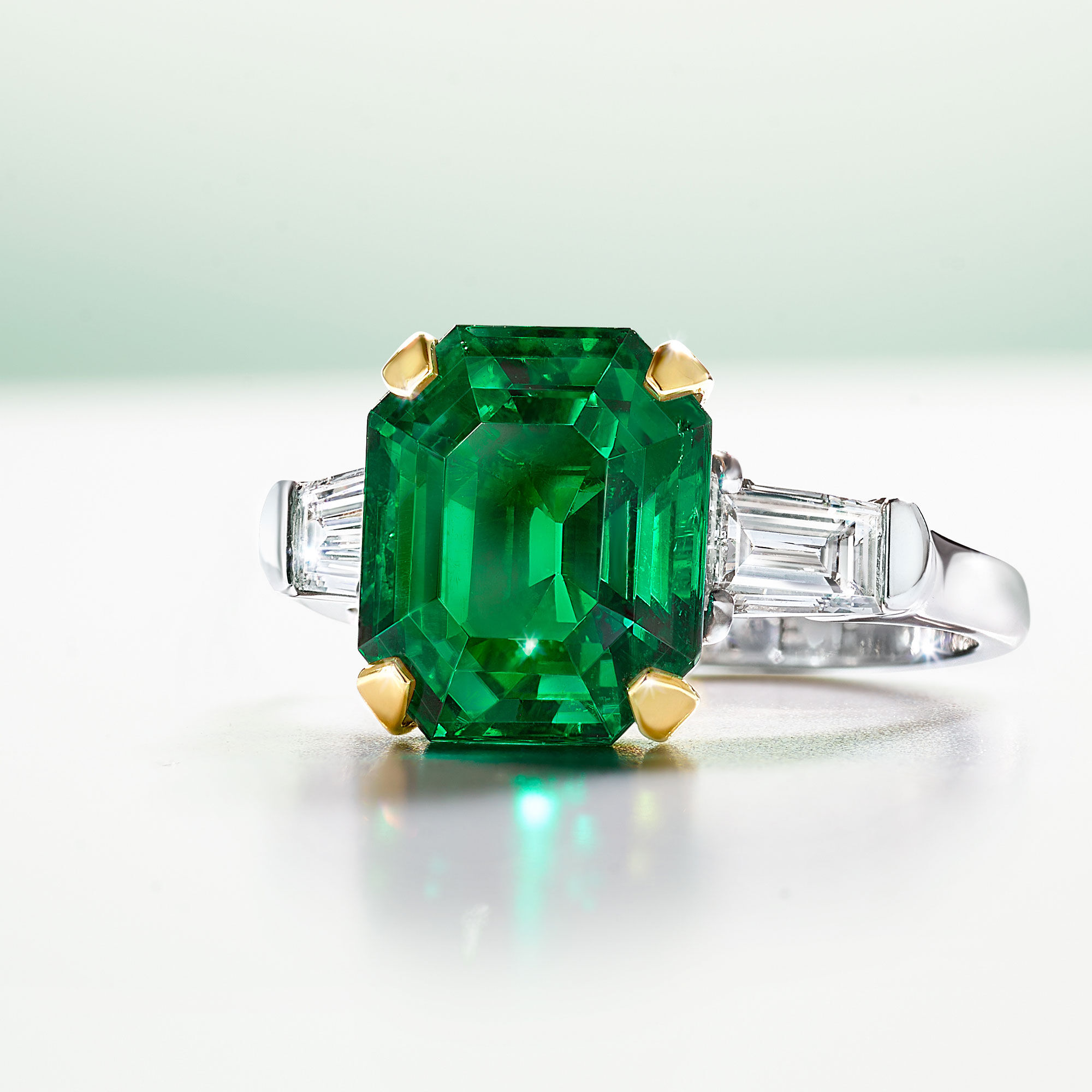 An emerald cut emerald ring with baguette cut side diamonds by Graff