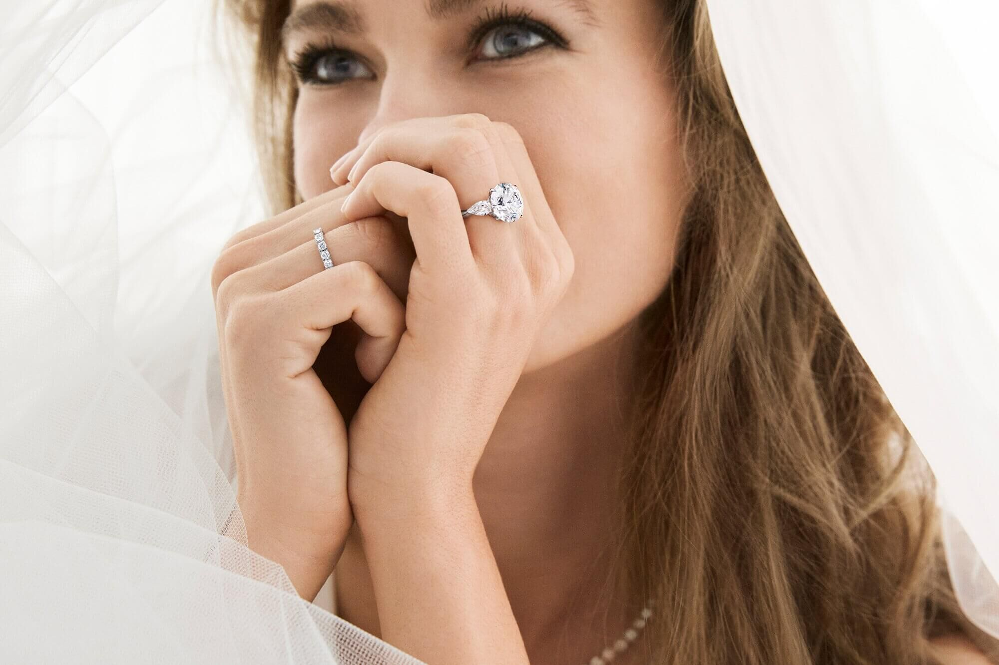 Model bride wears Promise Round Diamond Engagement Ring with pear shaped side stones and Castle Set Round Diamond Wedding Band from the Graff bridal collection.