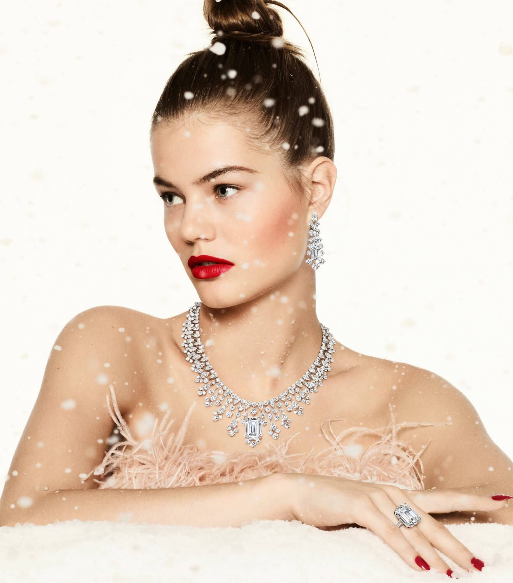 a lady wearing Graff white diamond high jewellery necklace, earrings and ring in a winter wonderland scene