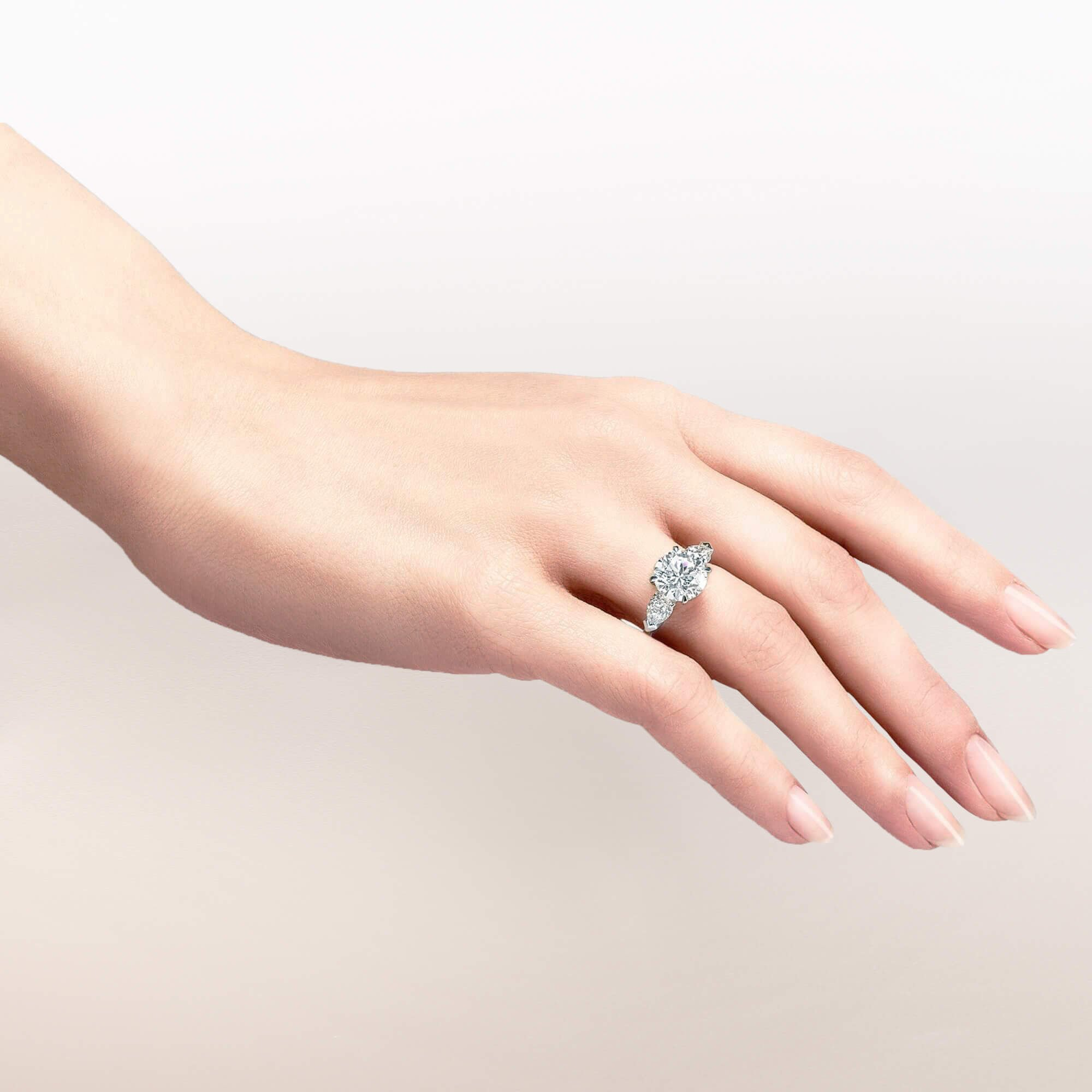 Close up of a models hand wearing a Graff round diamond engagement ring