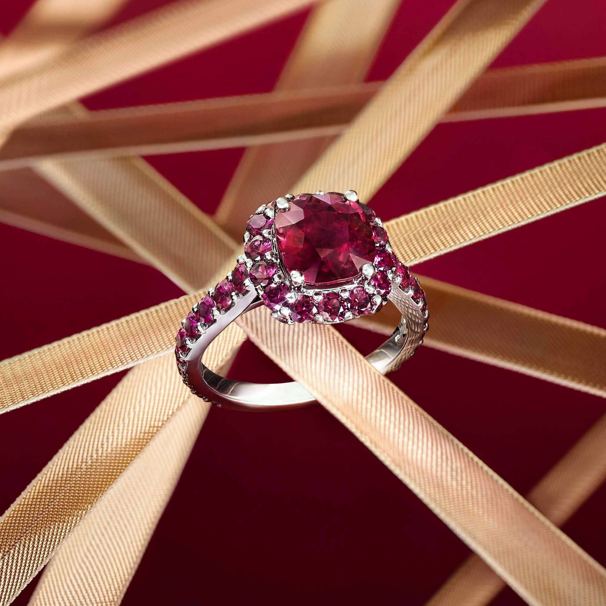 A Graff Ruby ring with gold ribbons on a red background
