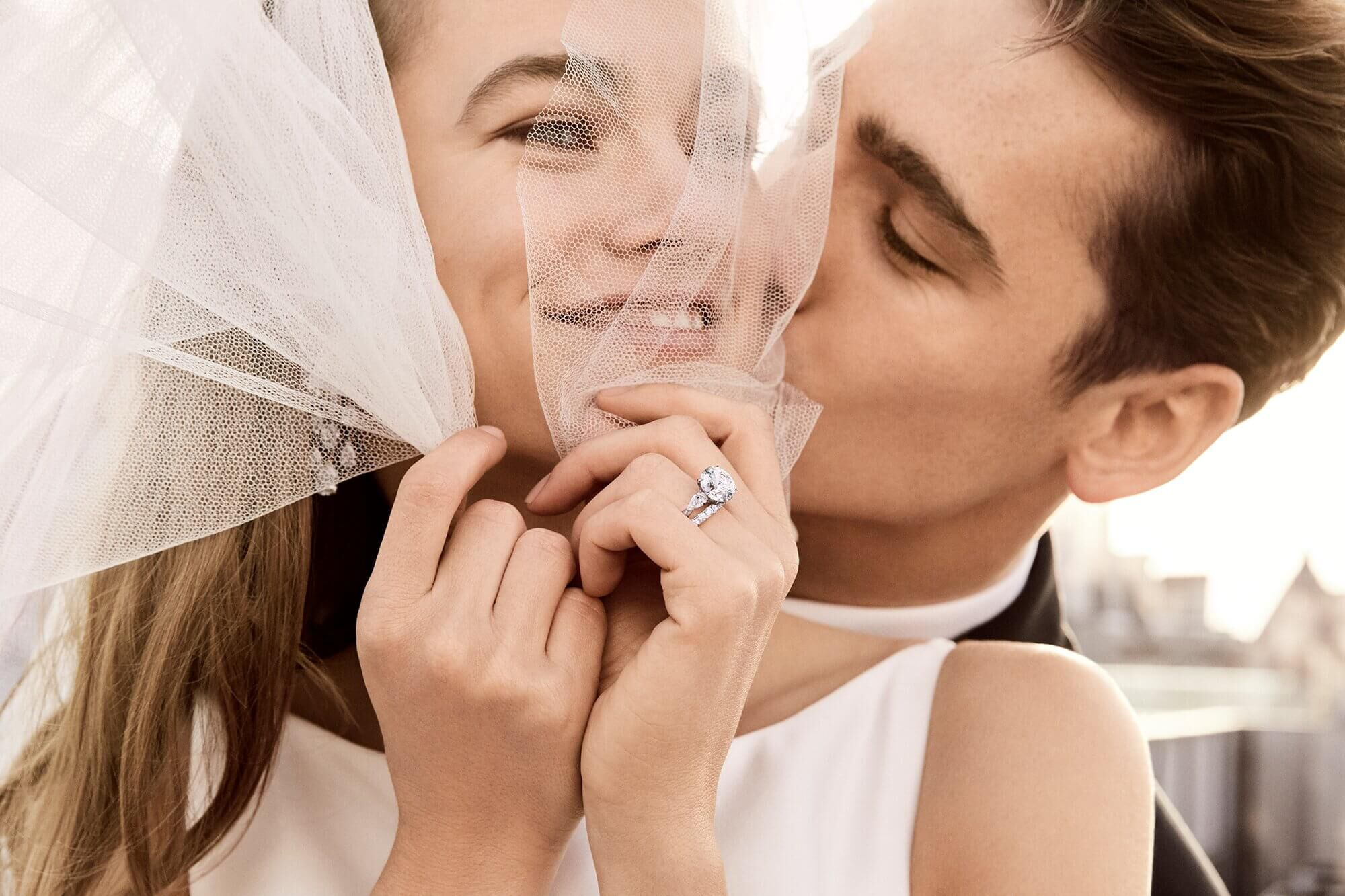 A man is kissing a lady wearing a Graff diamond engagement ring