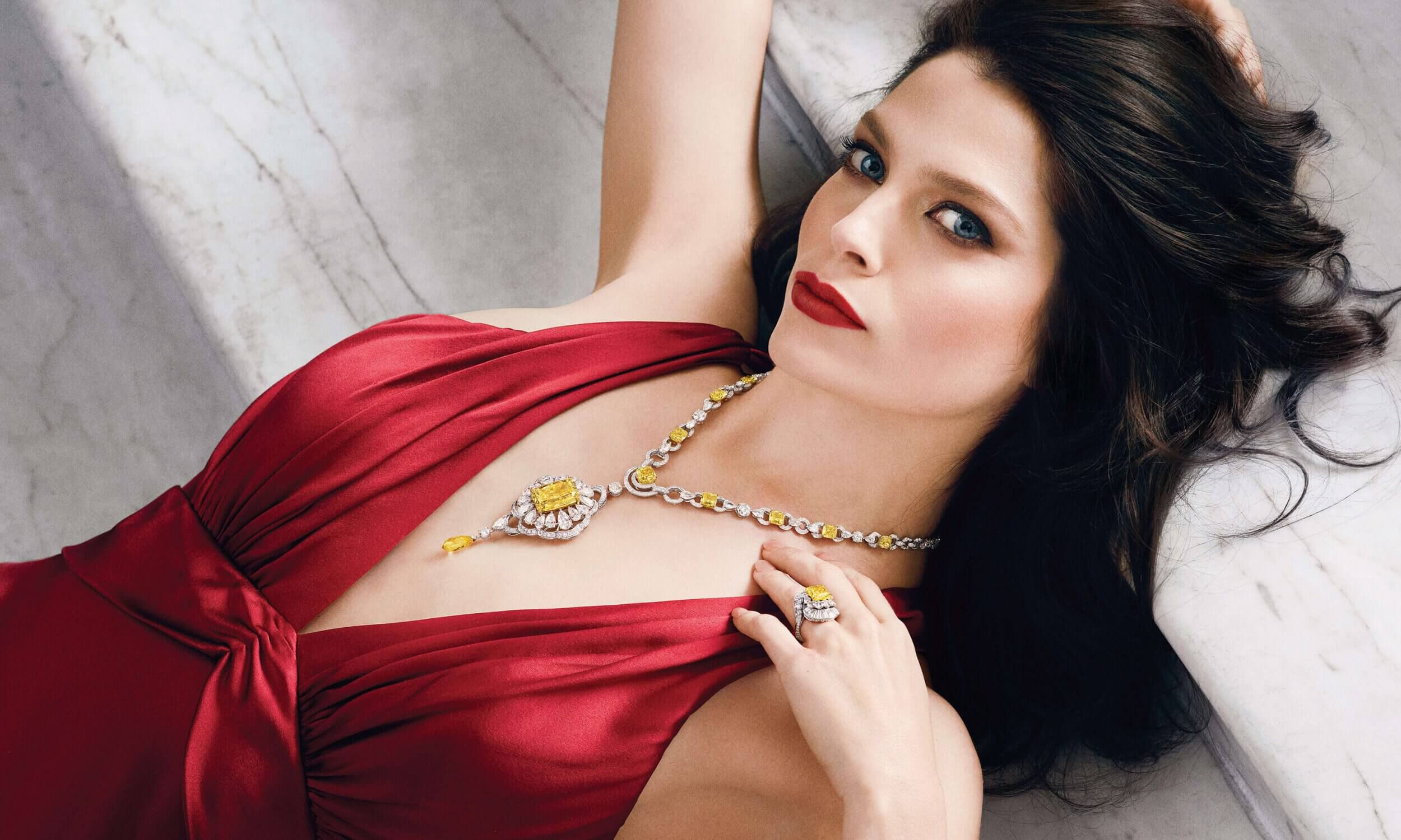 A lady in a red dress reclining wearing a Graff Diamonds Yellow and white diamond necklace featuring a 32 carat Fancy Yellow radiant cut diamond