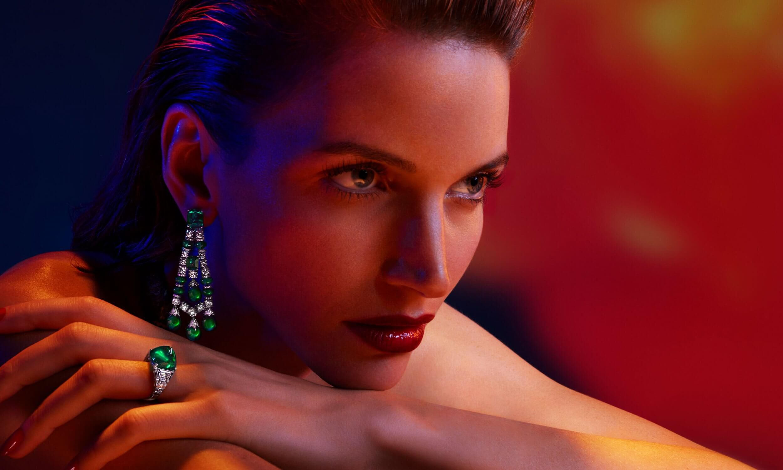 A model wears Graff high jewellery emerald and diamond earrings and am sugarloaf Colombian emerald ring.