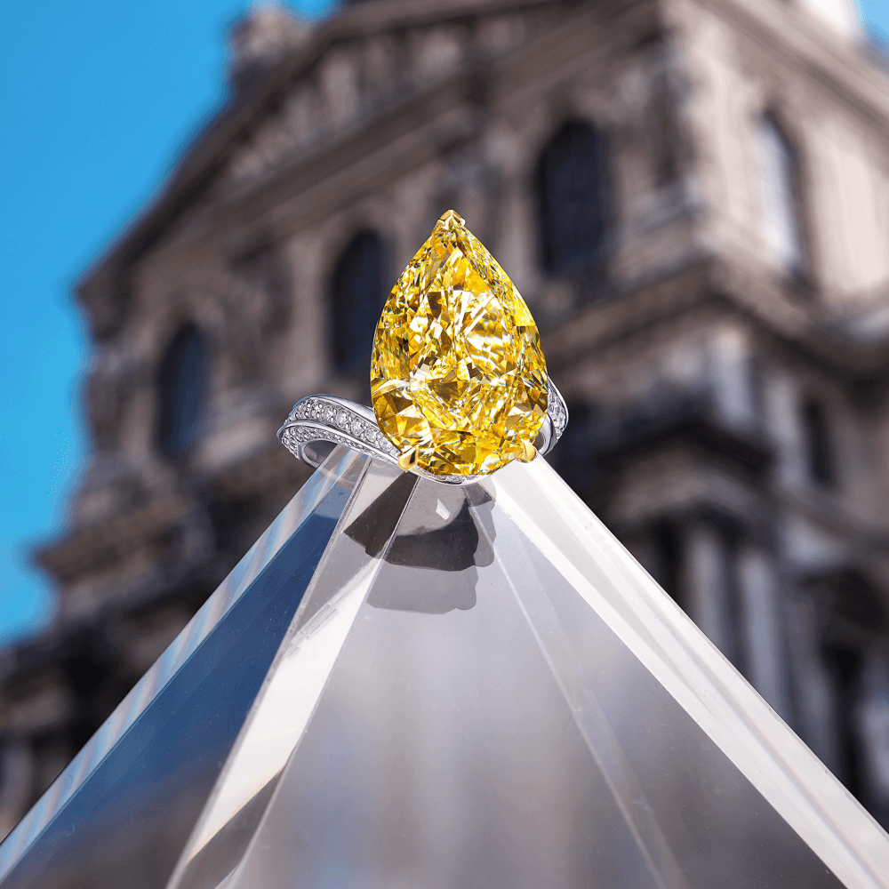 Graff Fancy Yellow Internally Flawless Pearshape Diamond High Jewellery Ring Set On A White Pave Twisted Band in front of a Gallery.