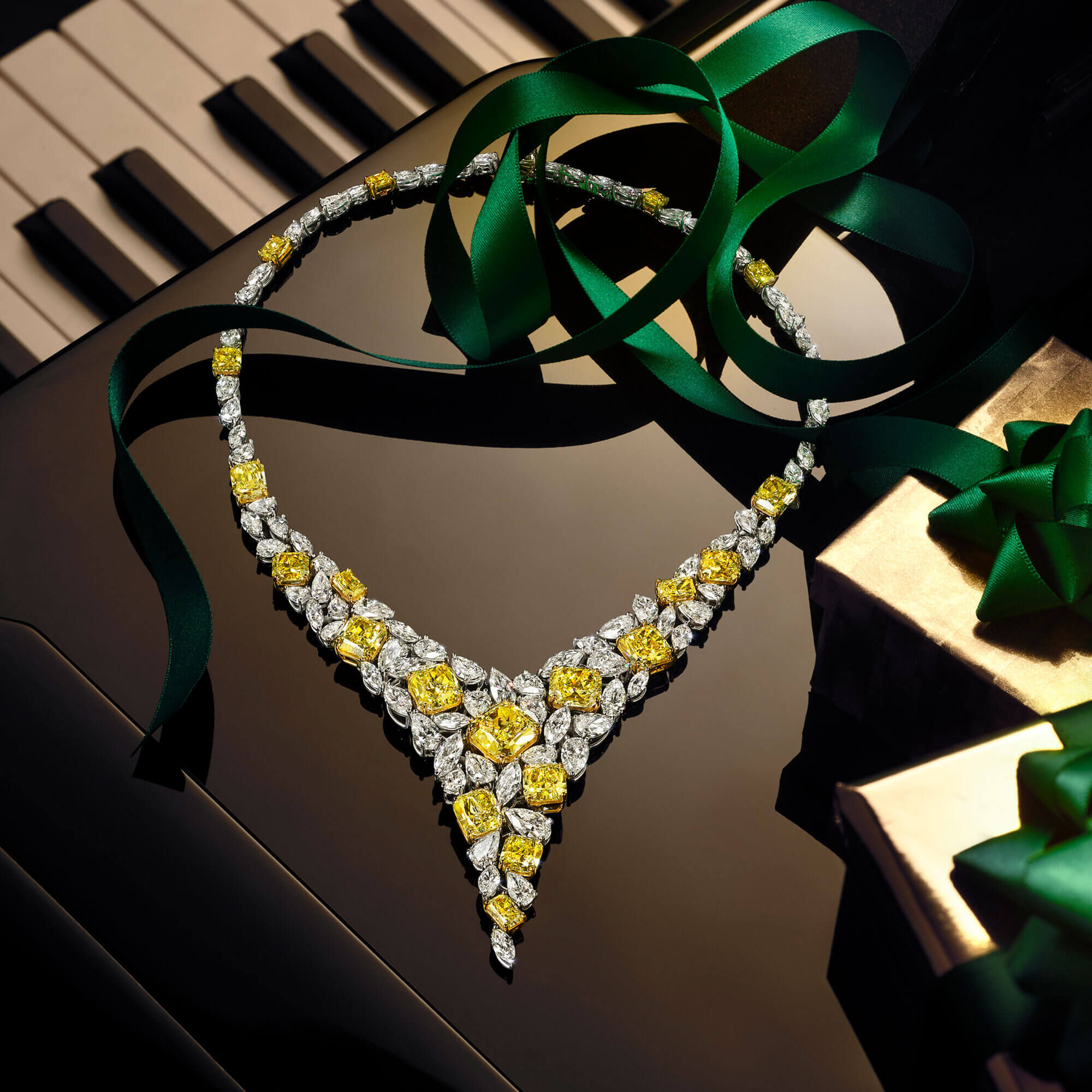Graff yellow and white diamond high jewellery necklace on a piano next to holiday season christmas gift boxes