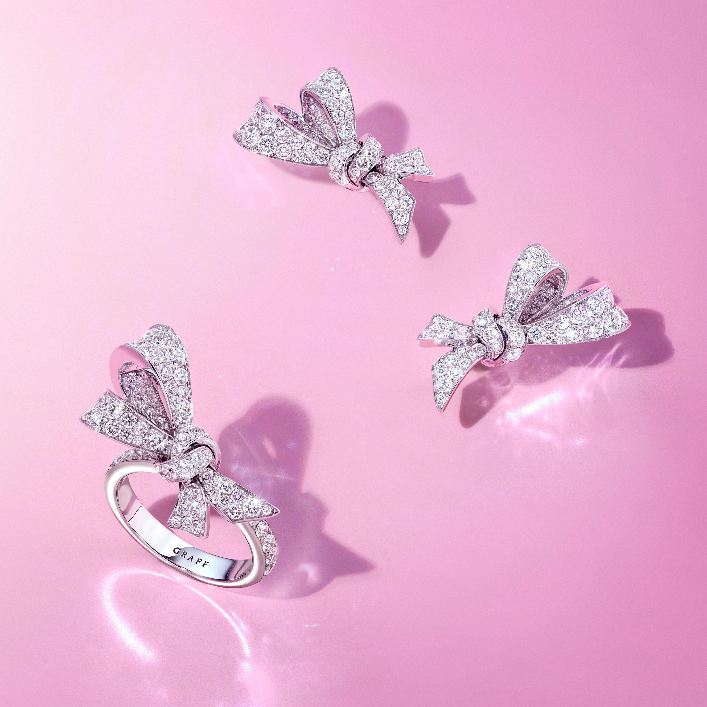 Graff Tilda's Bow diamond earrings and rings on a pink background