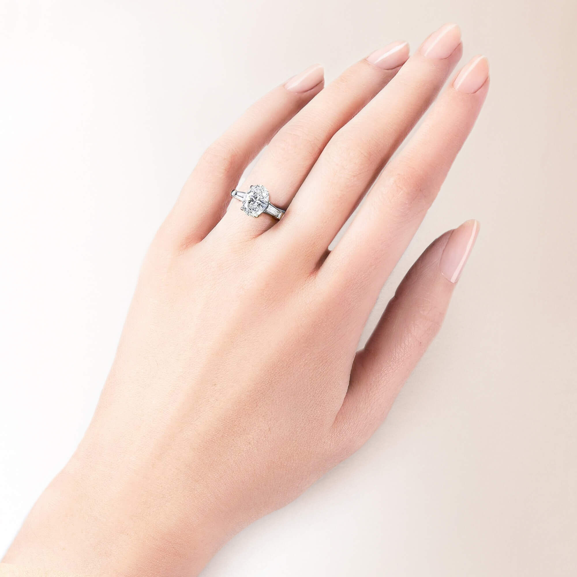 A models hand wearing a Graff oval shape diamond engagement ring