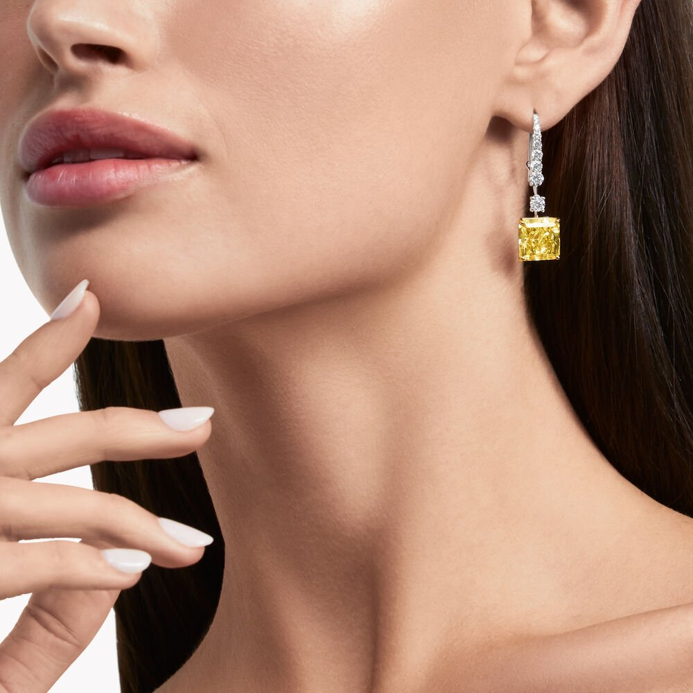 Close up of a model wearing a pair of Graff yellow diamond high jewellery earrings