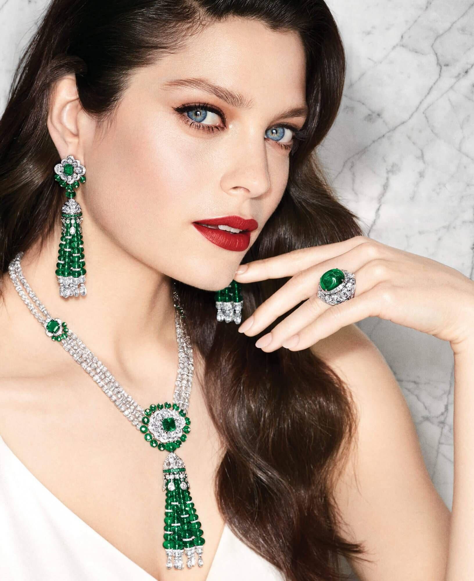 Model wears Graff Diamonds Beaded emerald and diamond tassel earrings with a beaded emerald and diamond tassel necklace