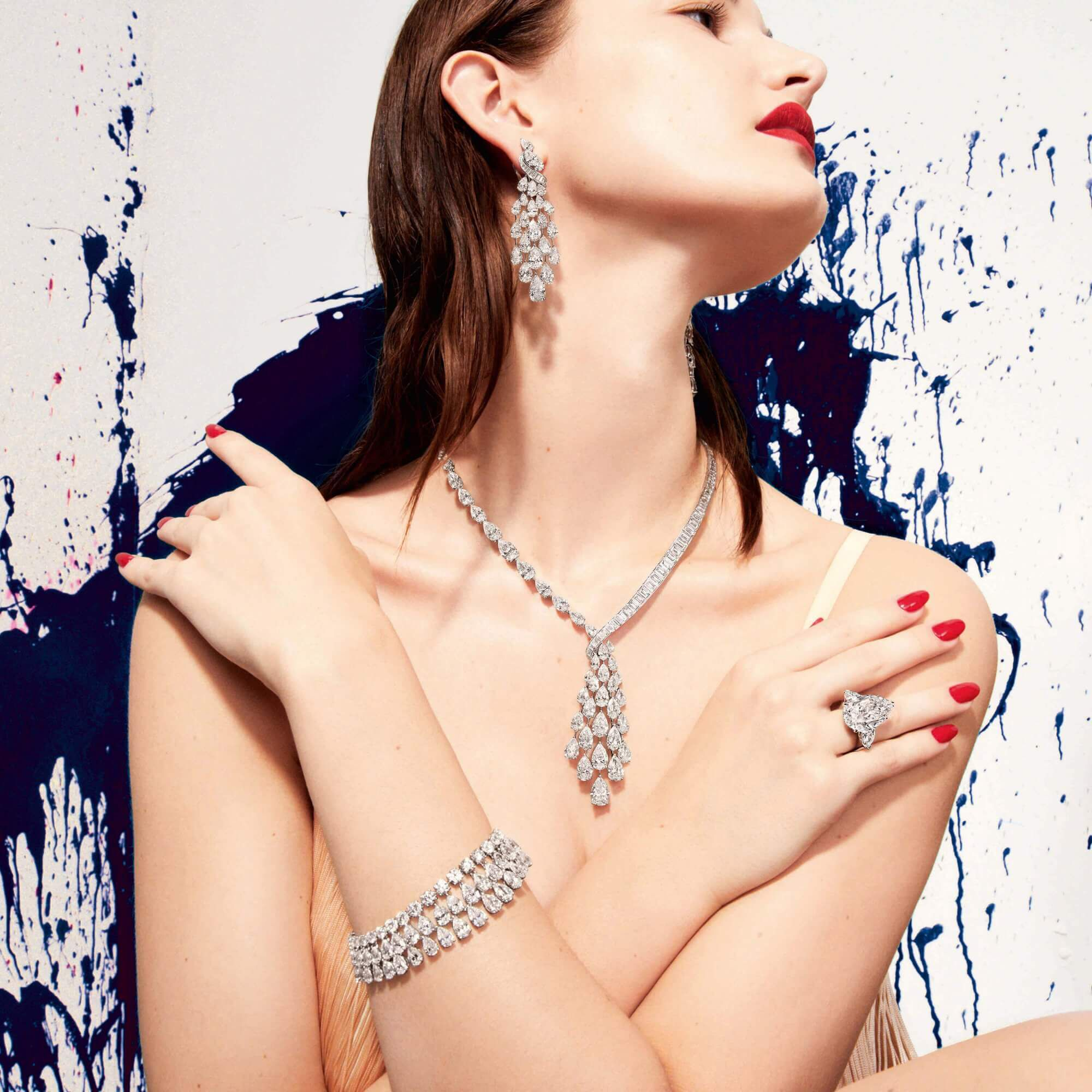 Model wears Graff Diamond necklace, earrings, bracelet and 14.02 carat pear shape diamond ring