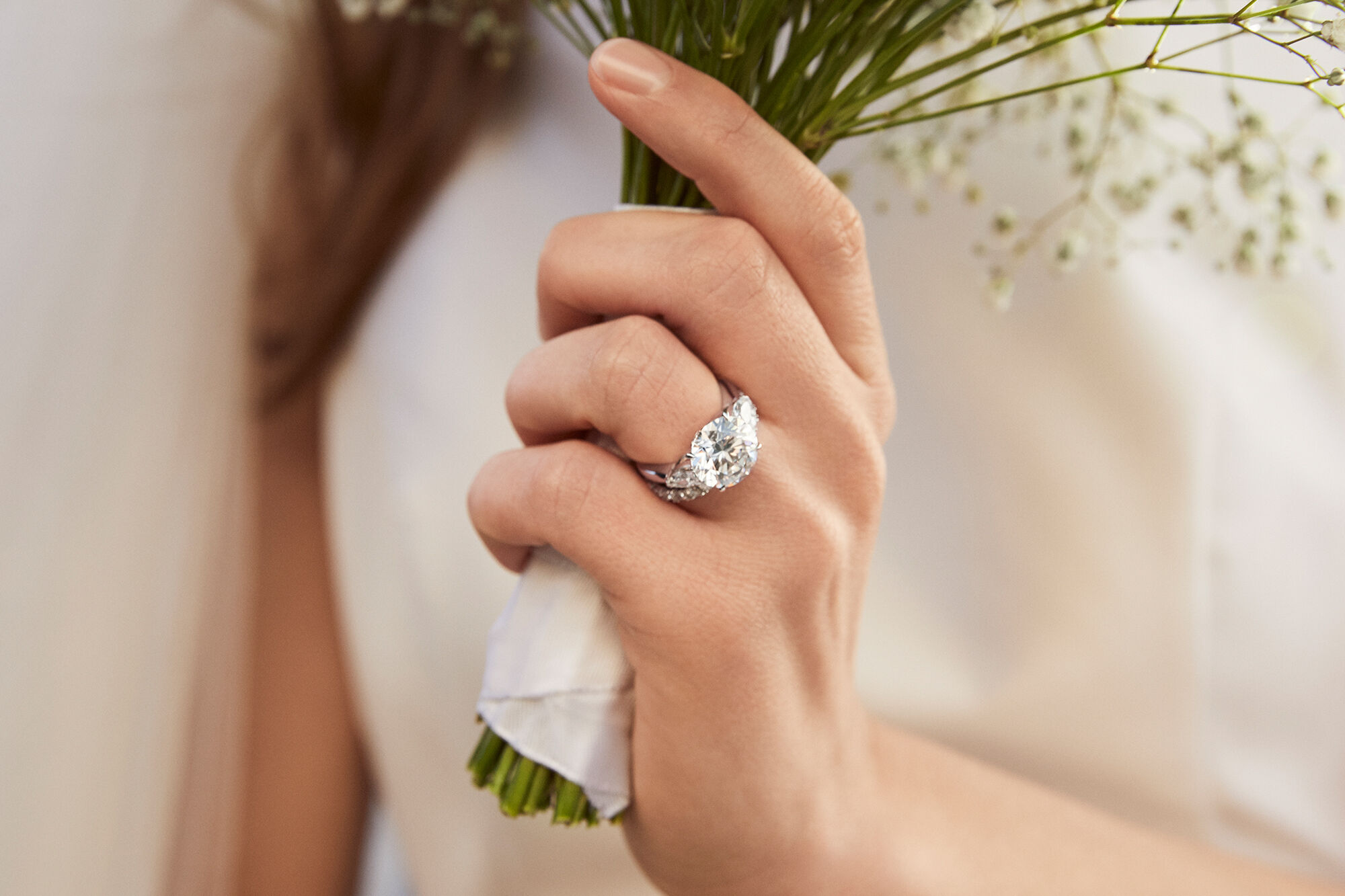 Close up of a model wearing a round diamond engagement ring by Graff holding a bunch of flowers