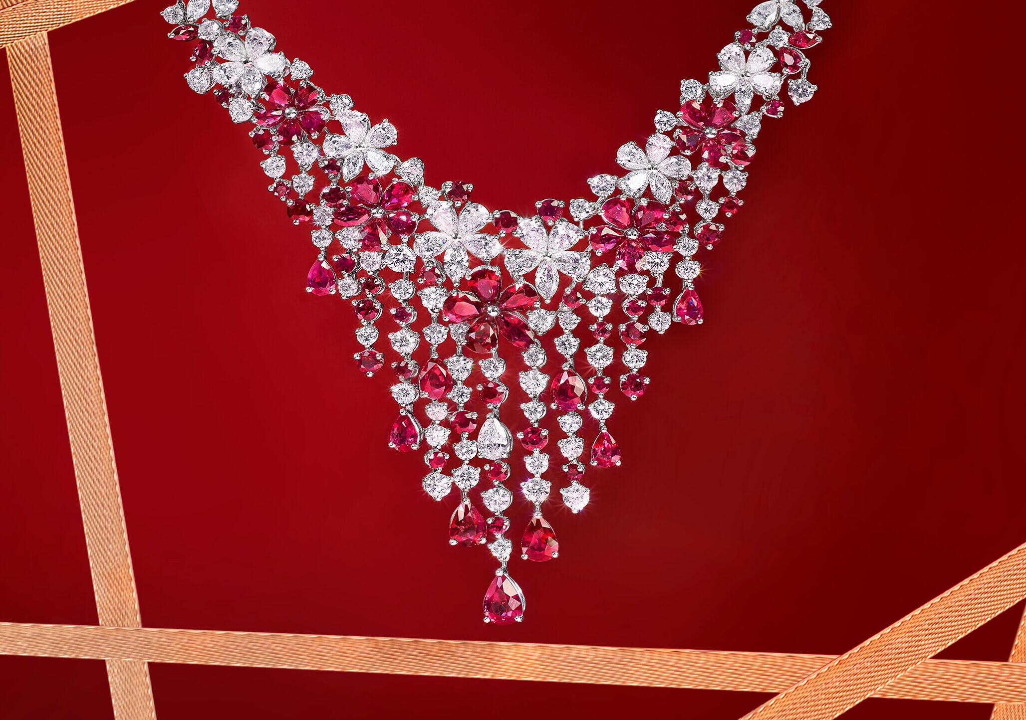 A Graff Carissa Collection Ruby and Diamond Necklace hanging in front of a red background with gold ribbons