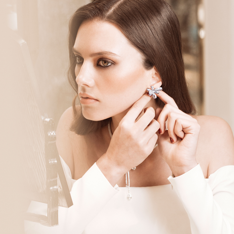 Close up of a model wearing Graff diamond earrings in a Graff boutique