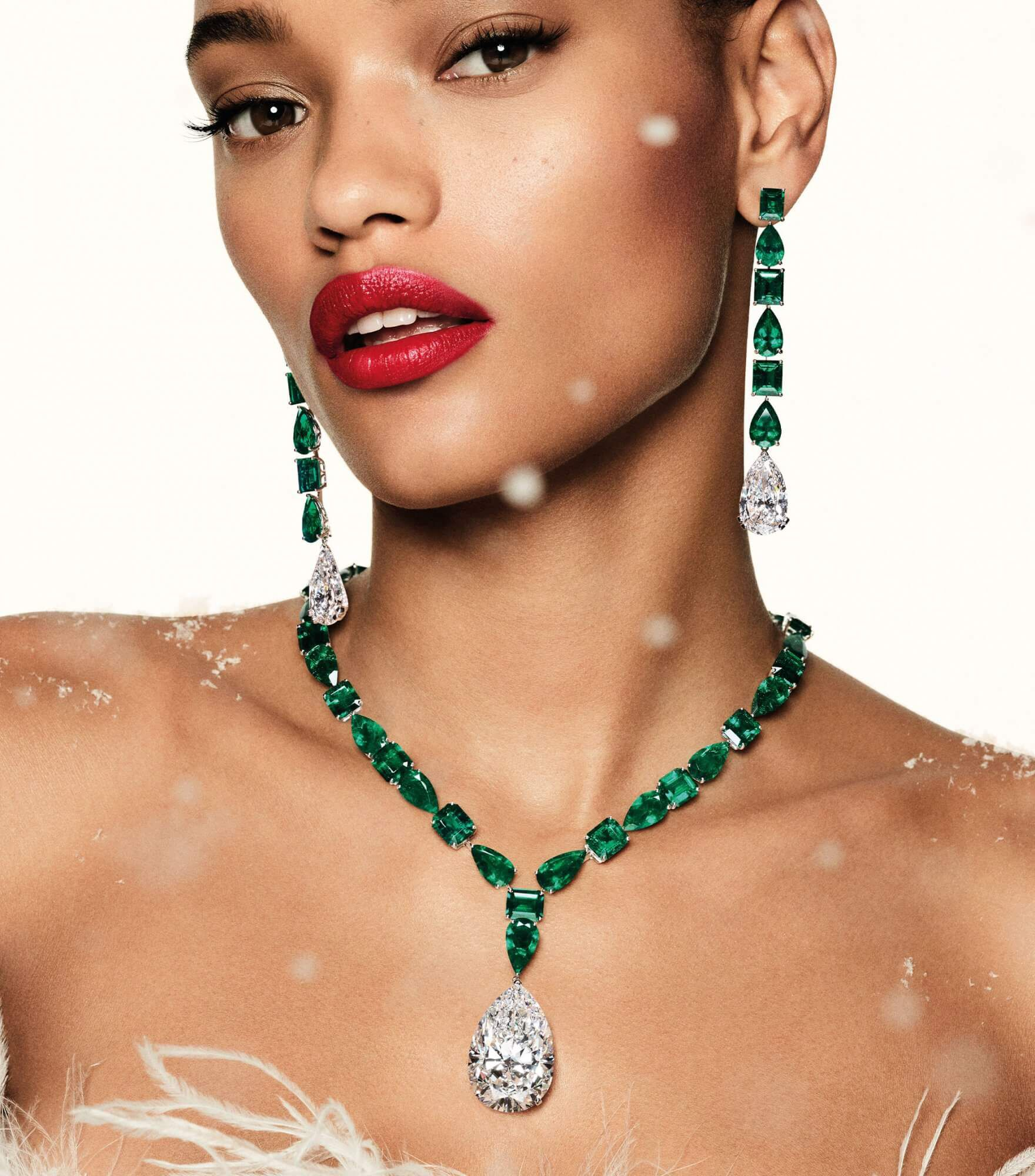 a lady wearing Graff emerald cabochon high jewellery necklace and earrings