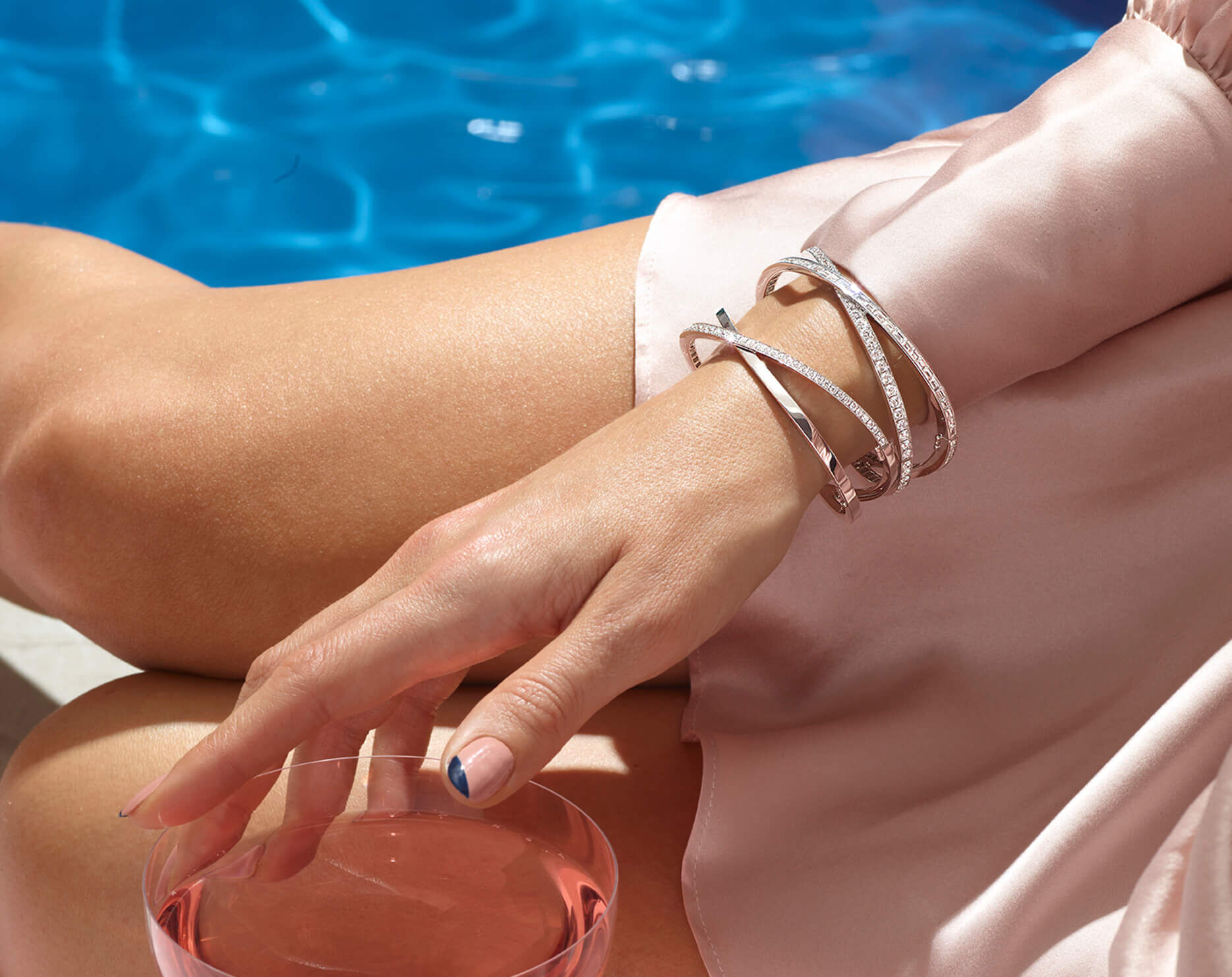 A lady sitting beside a pool wearing Graff Spiral Collection stackable bangles and rings