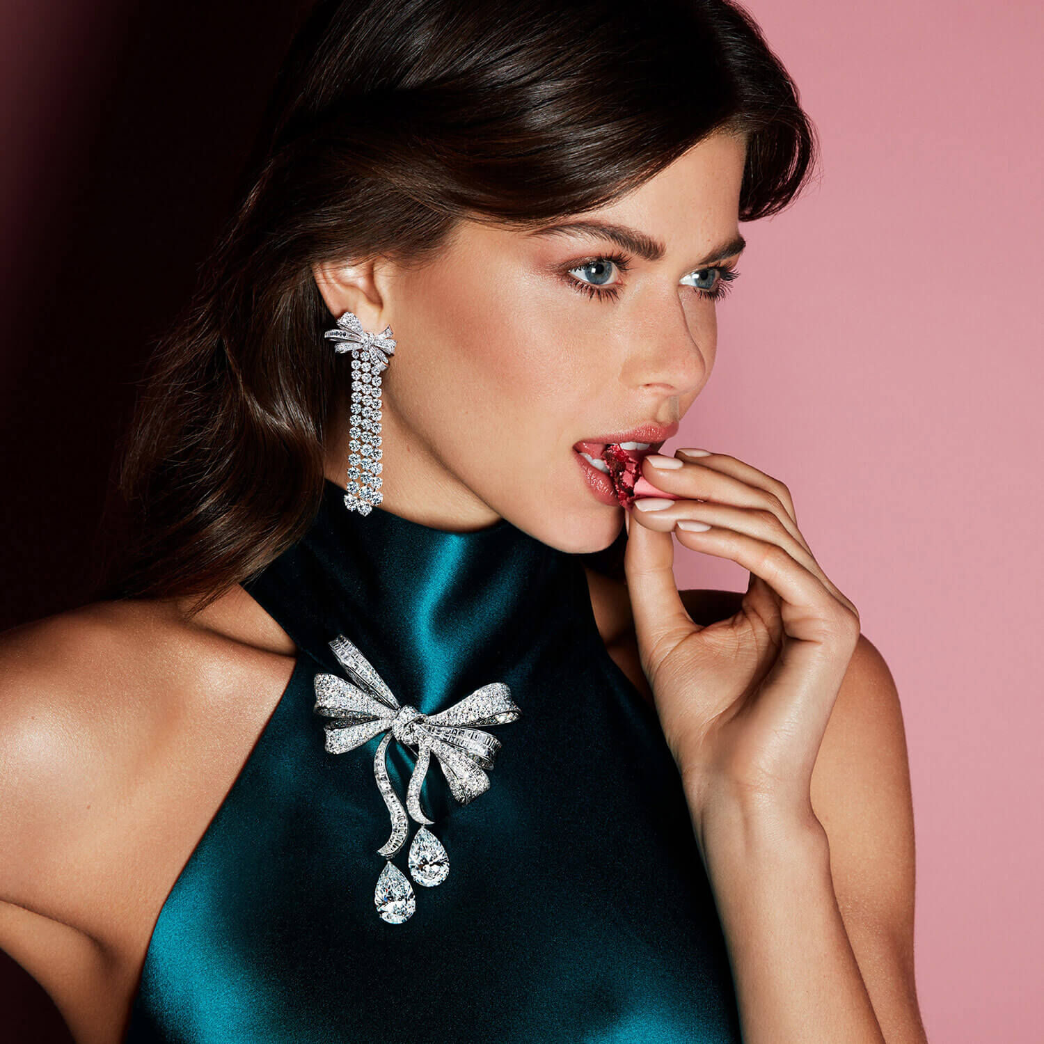 A lady on a pink background wearing ornate bow styled diamond necklace and earrings