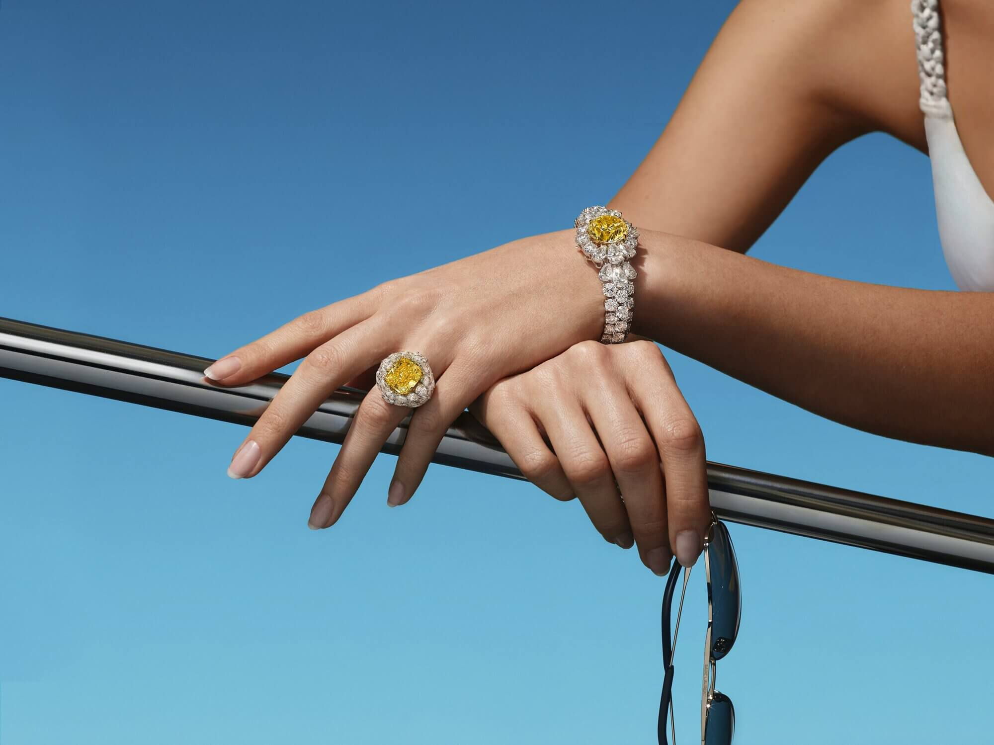 A lady on a boat wearing a yellow and white diamond Bracelet and ring from the Graff high jewellery collection