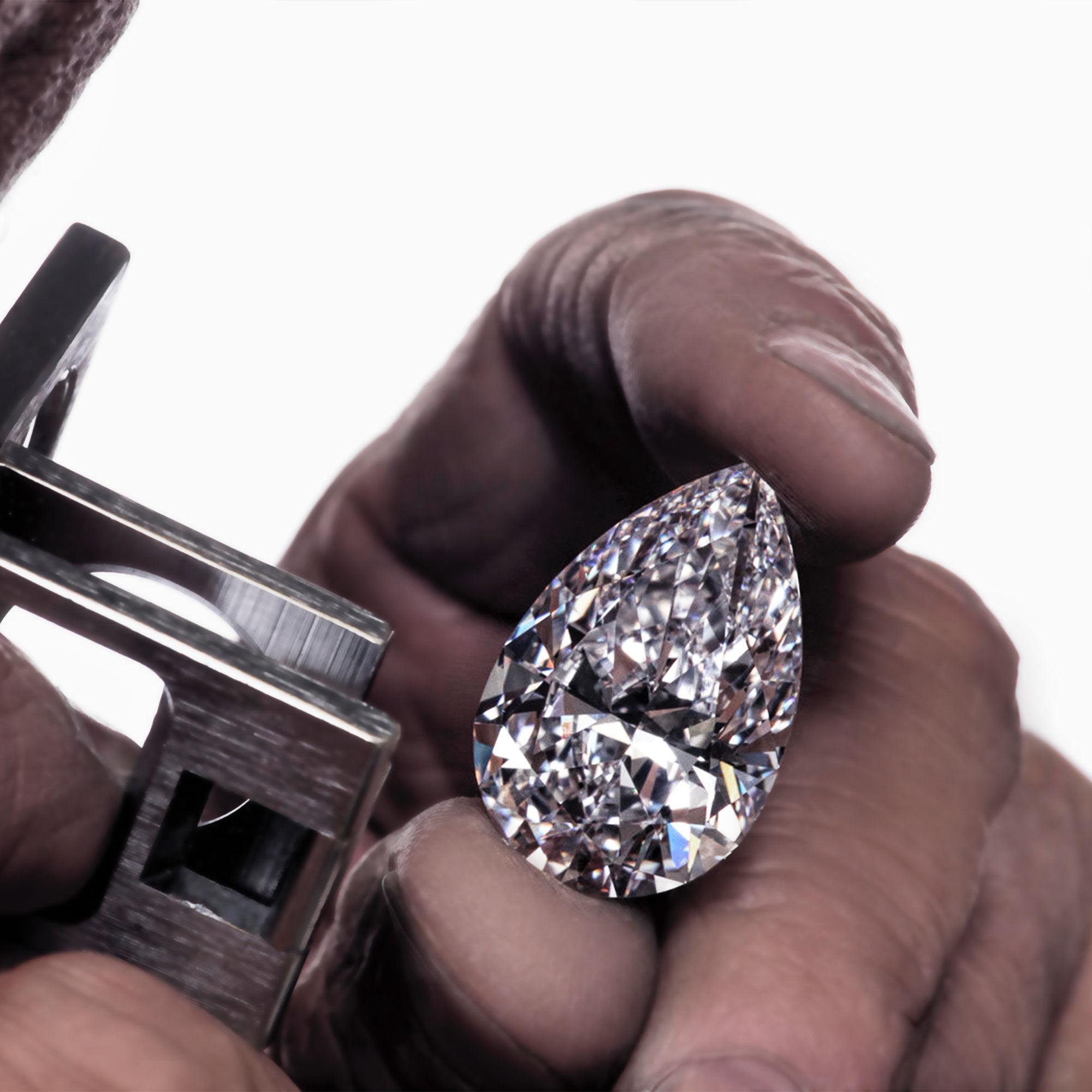Close up of a Graff craftsman investigating a pear shape diamond through a loupe