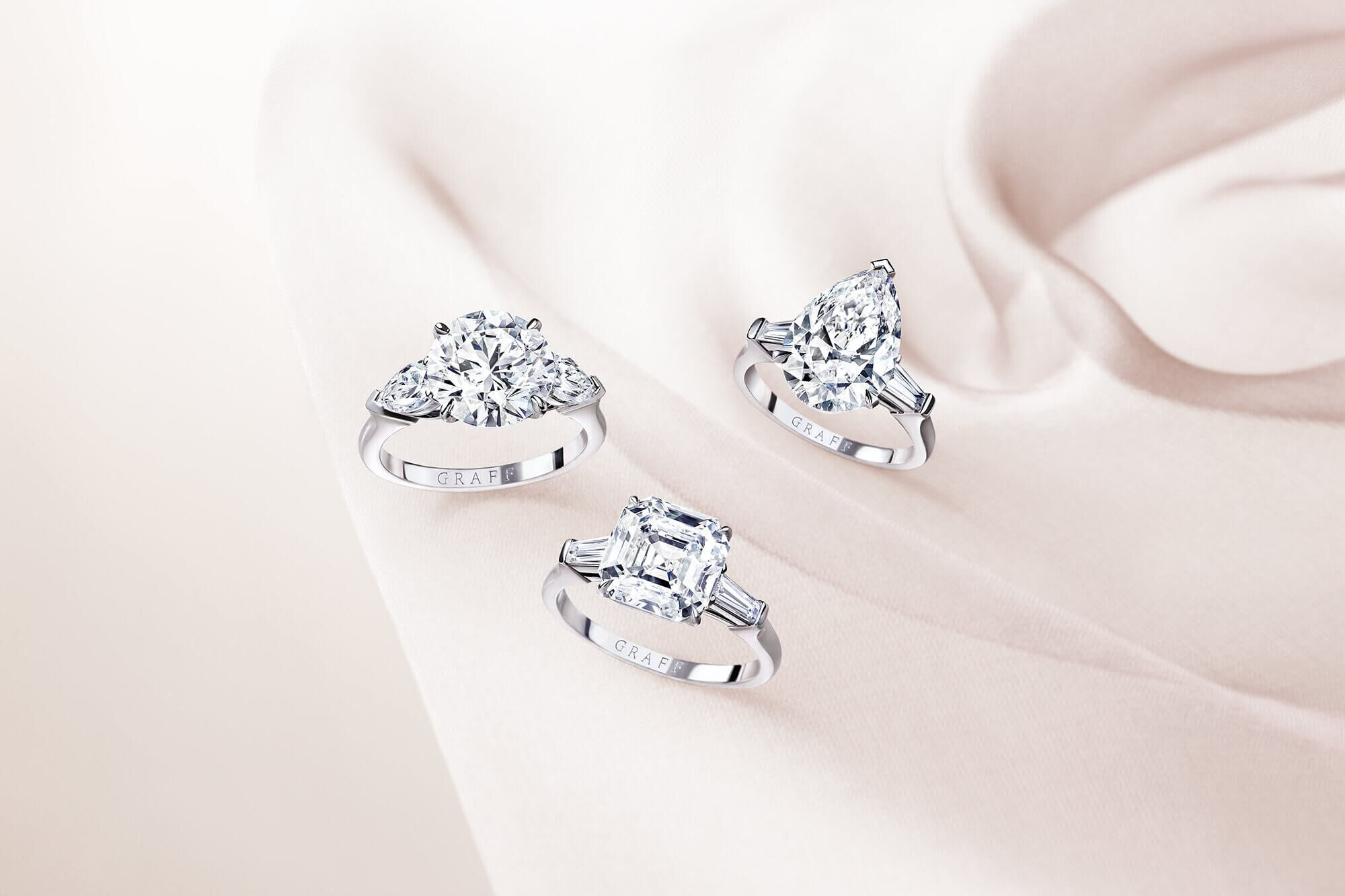 Three promise diamond engagement rings by Graff on a silk fabric