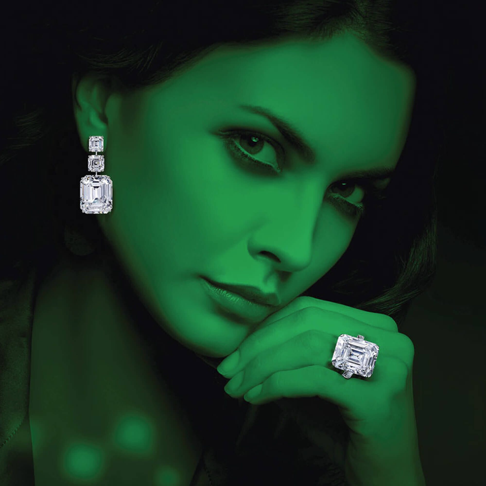 Model with green effect wearing Graff high jewellery emerald cut earrings and emerald cut solitaire ring.