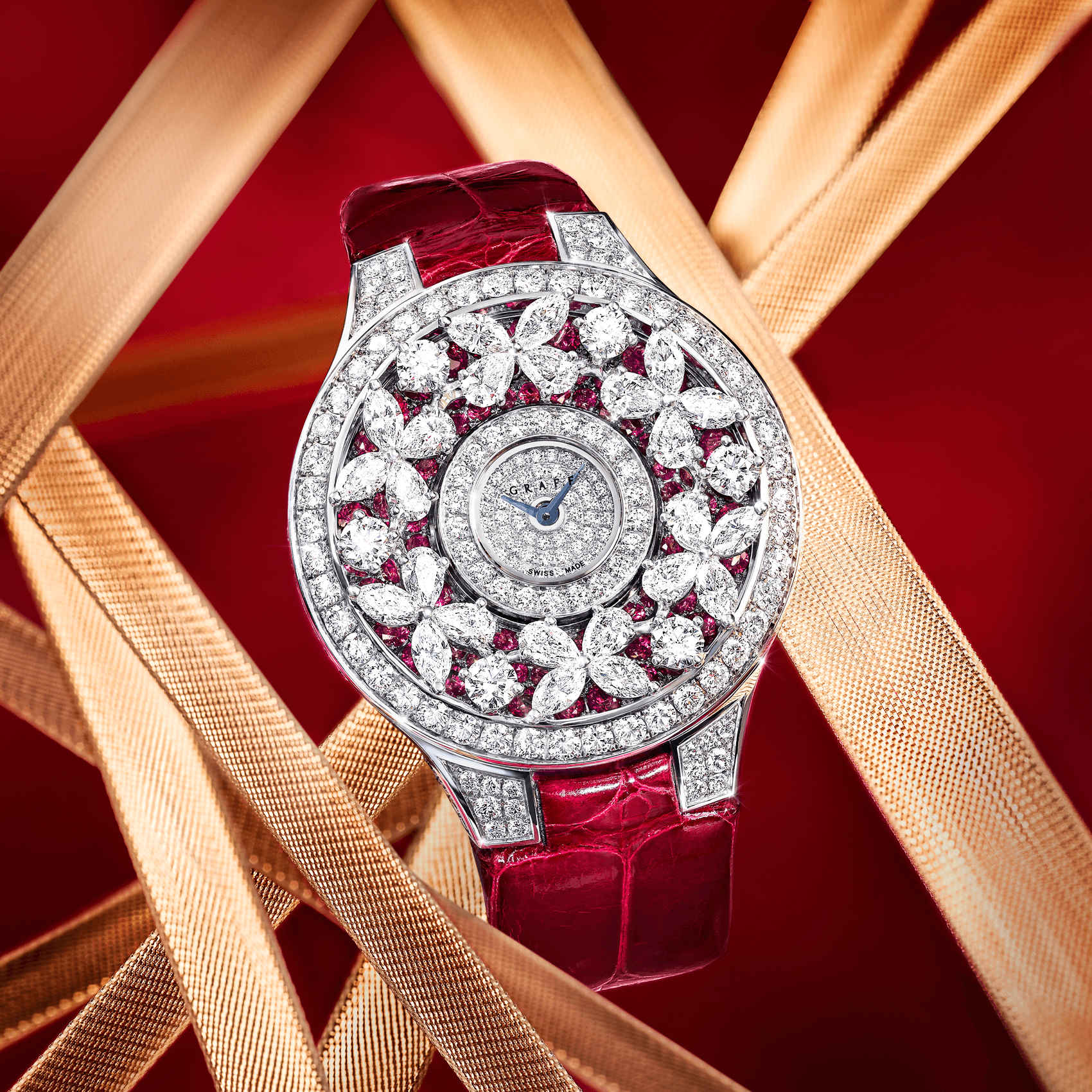 A Graff Classic Butterfly Diamond on Ruby Watch with red leather Strap on a red background with gold ribbons