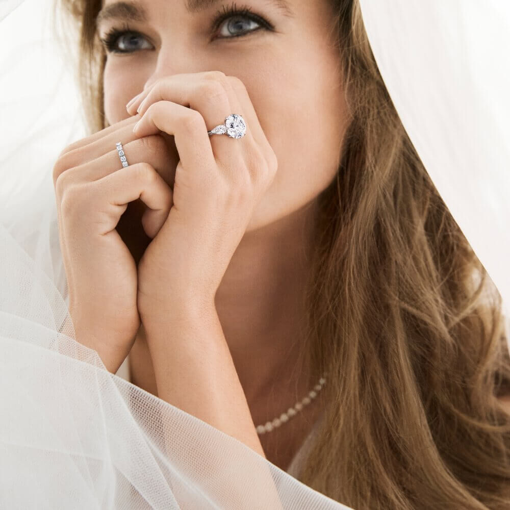 A  model wearing Graff diamond engagement ring and wedding band