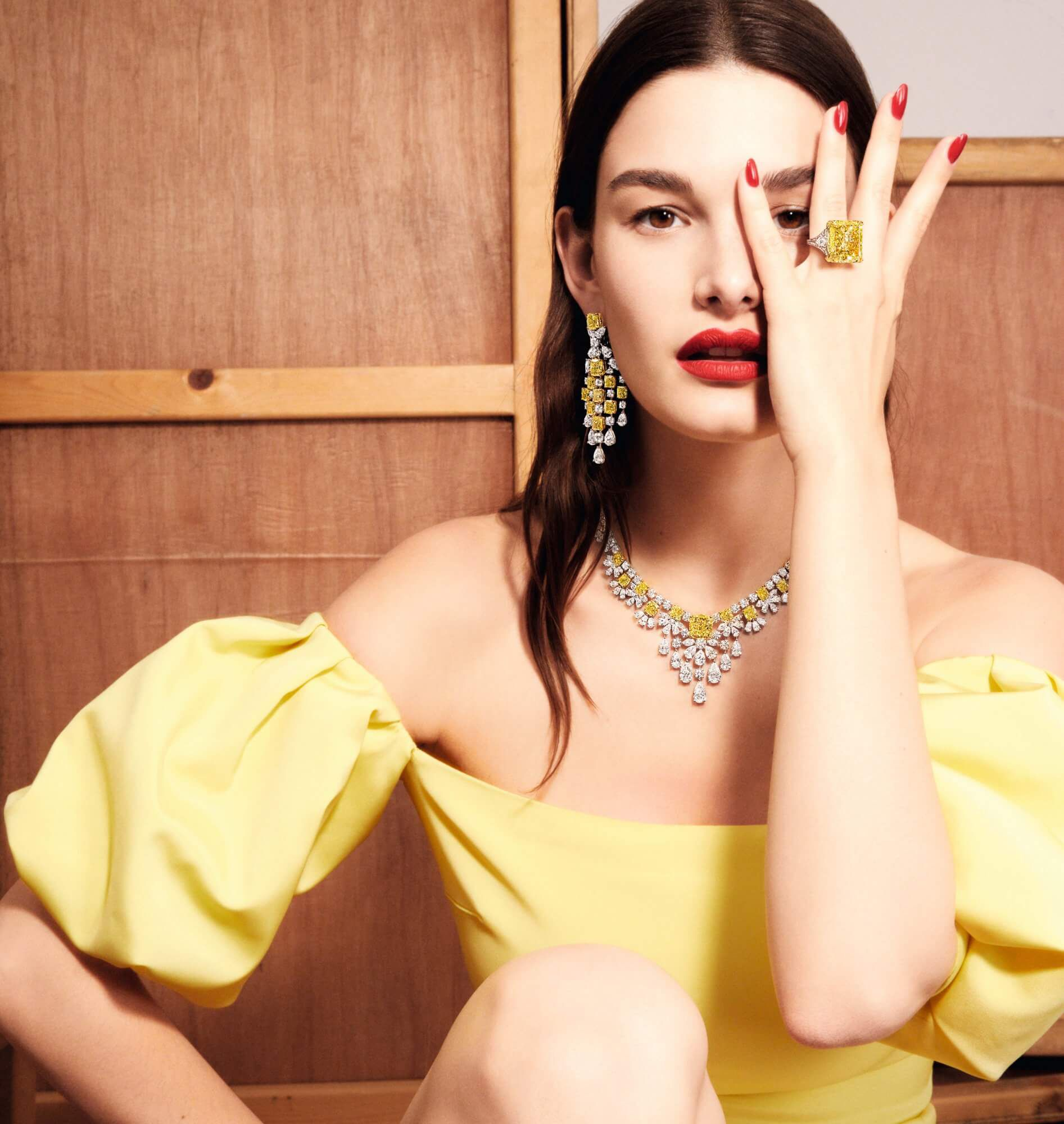 Model wears Graff yellow and white diamond high jewellery earrings and ring
