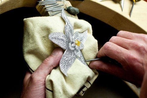 A diamond flower brooch in the hand of a graff craftsman