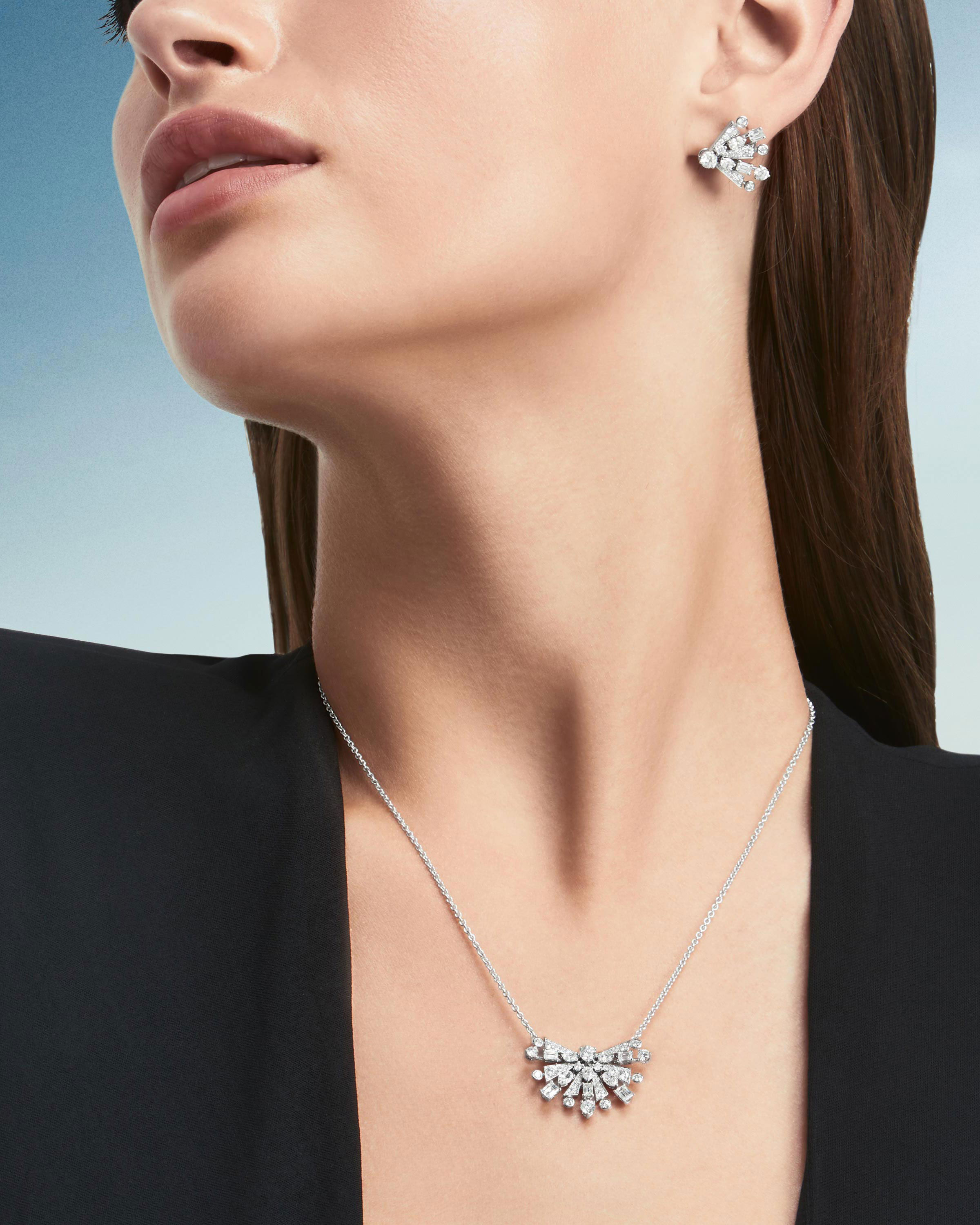 Close up of a model wearing the Graff New Dawn jewellery collection diamond earrings & pendant