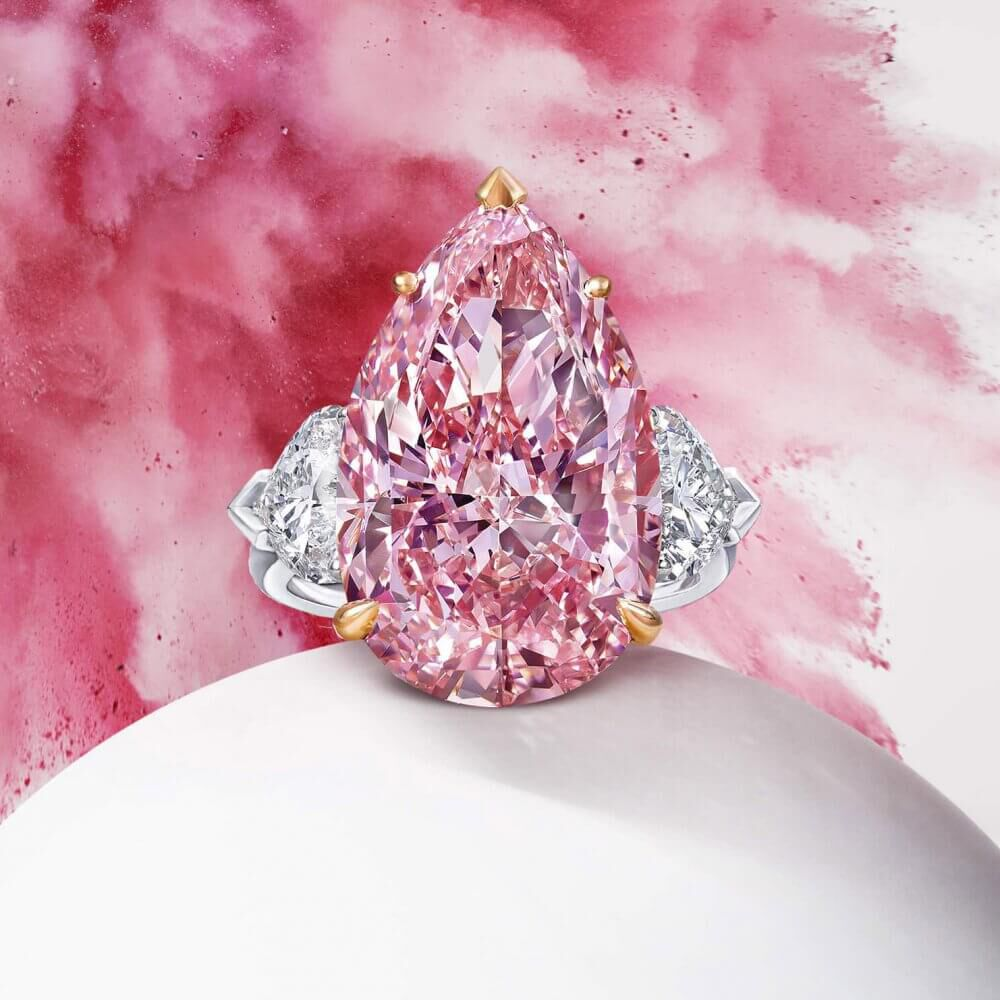 A Graff ring featuring a Fancy Vivid Pink Internally Flawless pear shape diamond and heart shape white diamond shoulder stones with pink explosion background