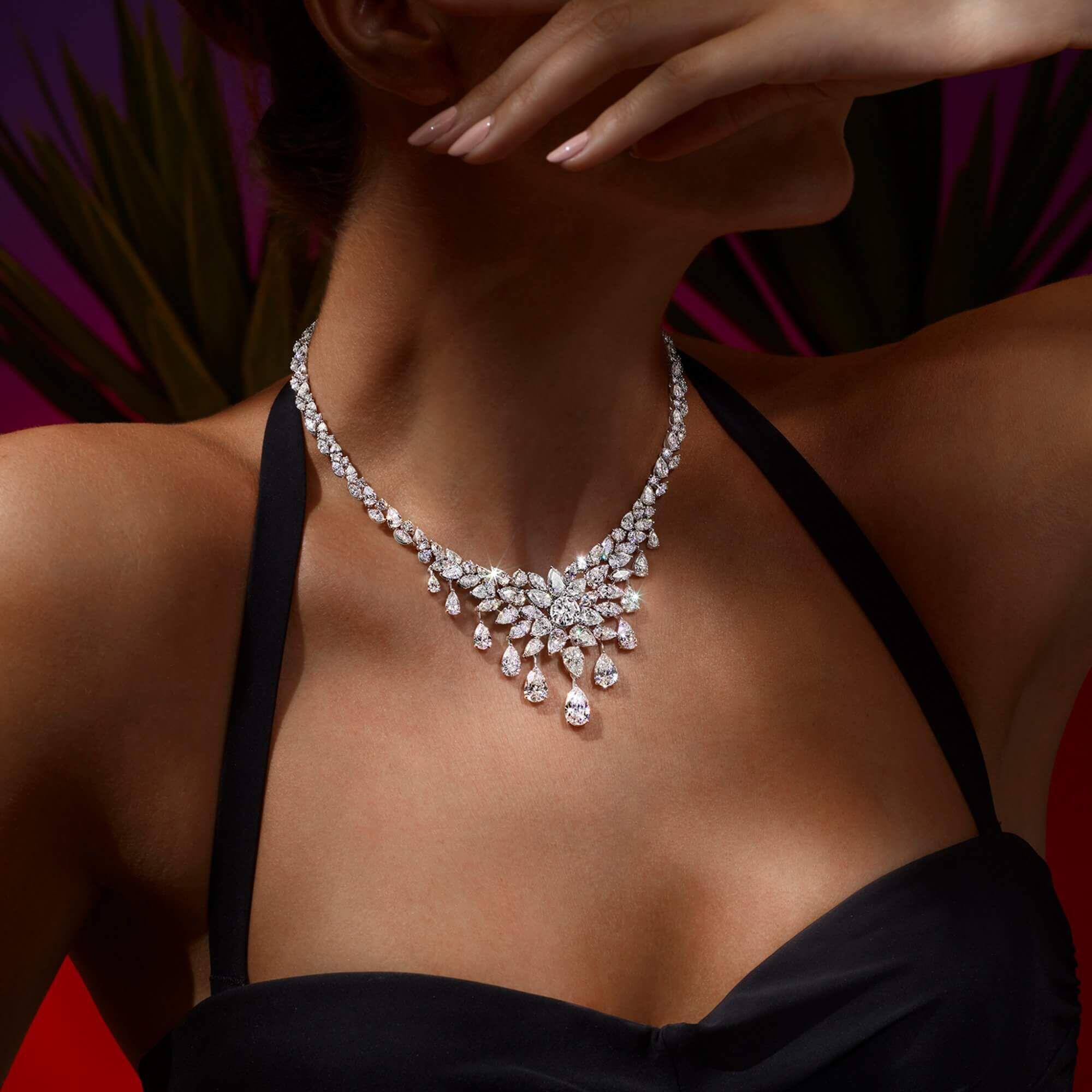A model in black swimsuit wearing a Graff diamond necklace