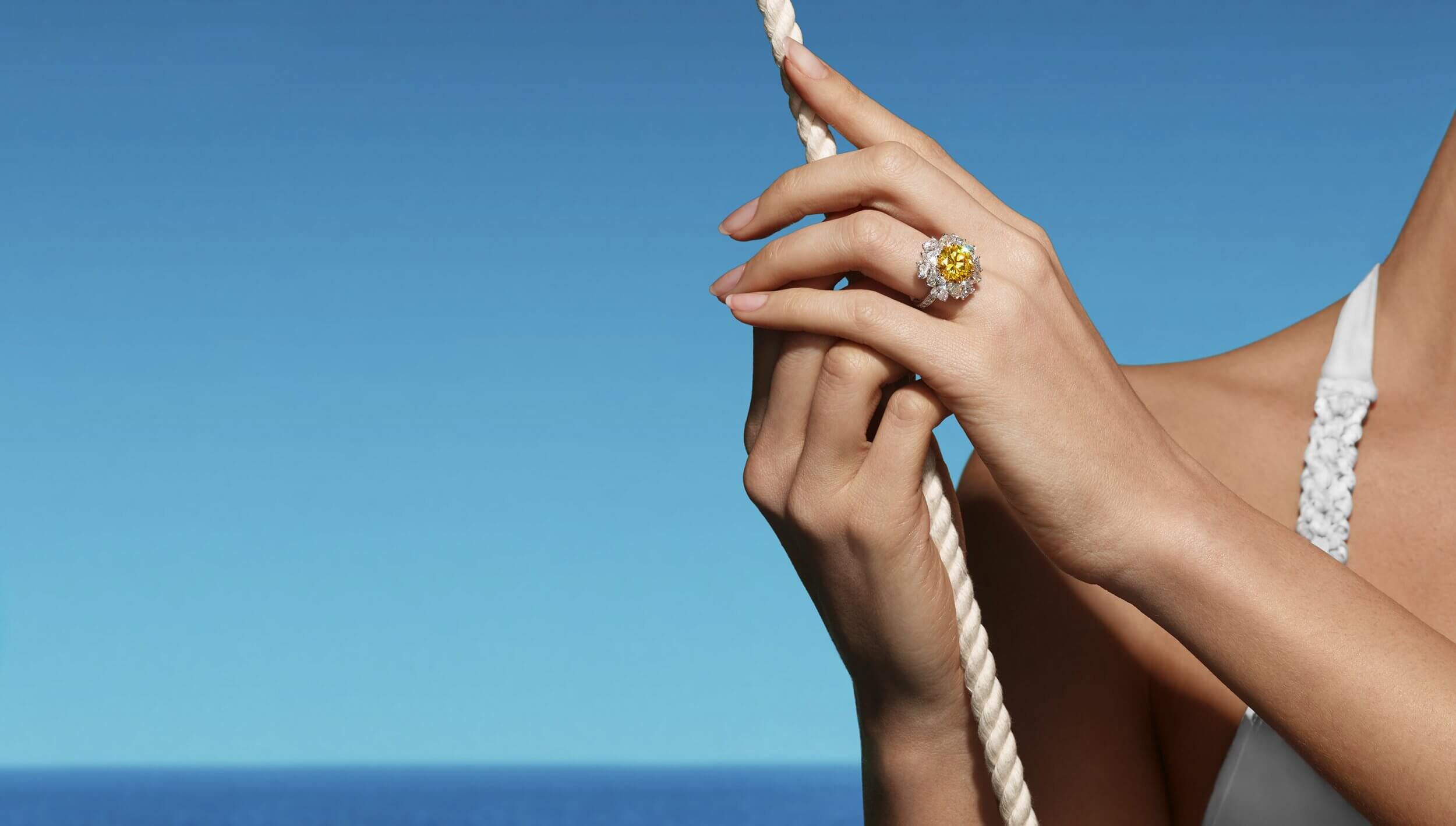 A lady on a boat wearing a yellow diamond ring from the Graff high jewellery collection