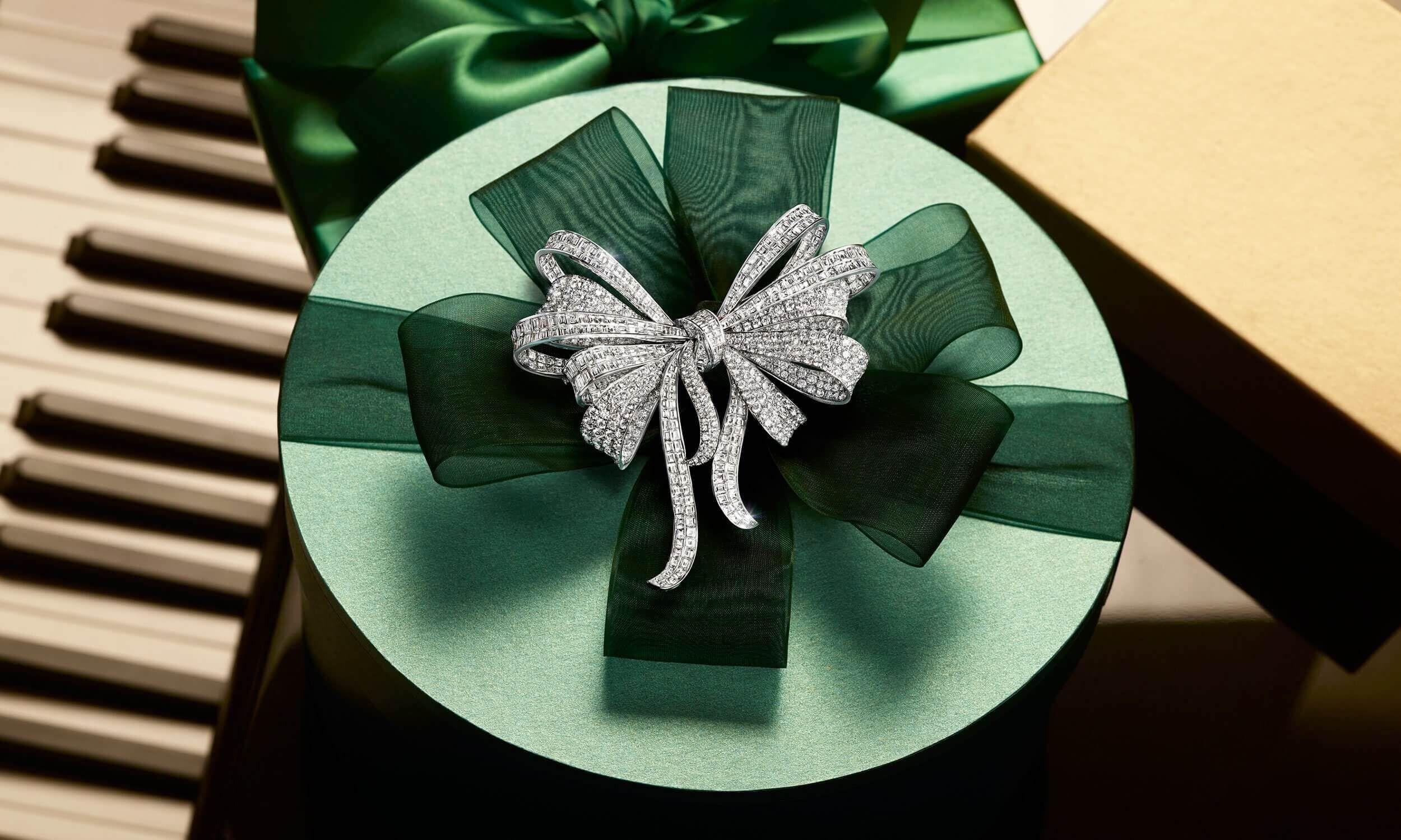 A Graff Diamond Bow Brooch on a holiday season Christmas green gift box