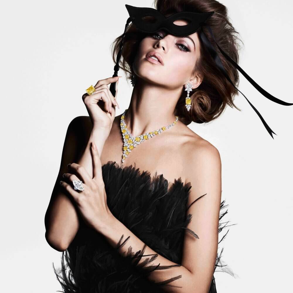 A model wearing Graff yellow and white diamond high jewellery earrings ring and necklace and a diamond ring in a black gown holding a mask