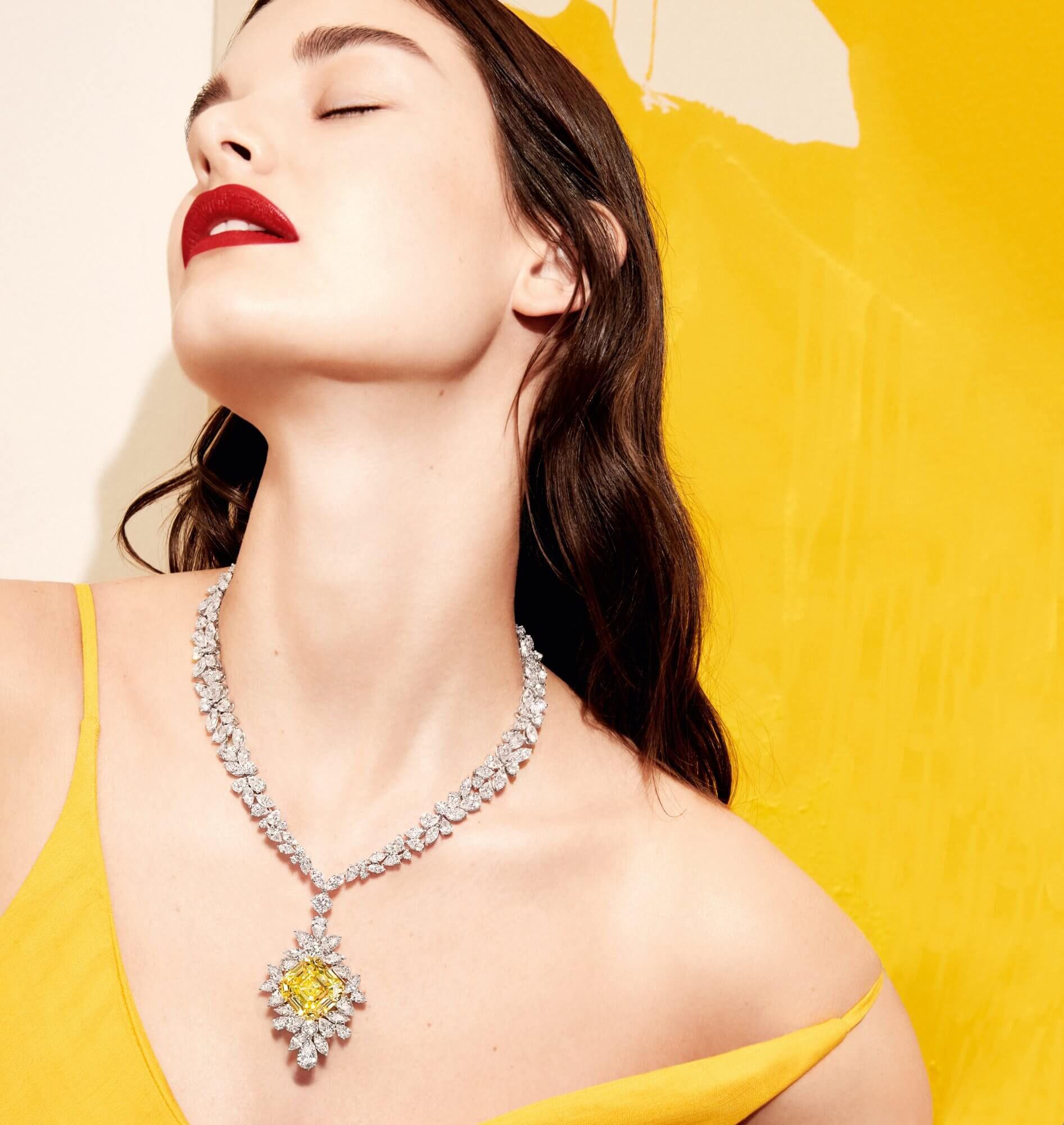 Model wears Graff yellow and white diamond high jewellery necklace featuring a 53.94 carat Fancy Intense Yellow emerald cut diamond
