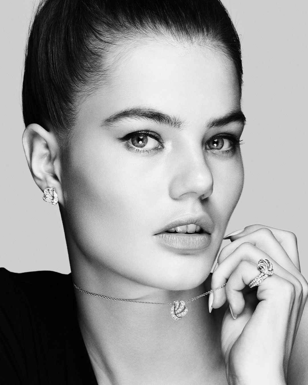 Close up of a black and white photo of a model wearing the Graff Tilda's Bow diamond jewellery