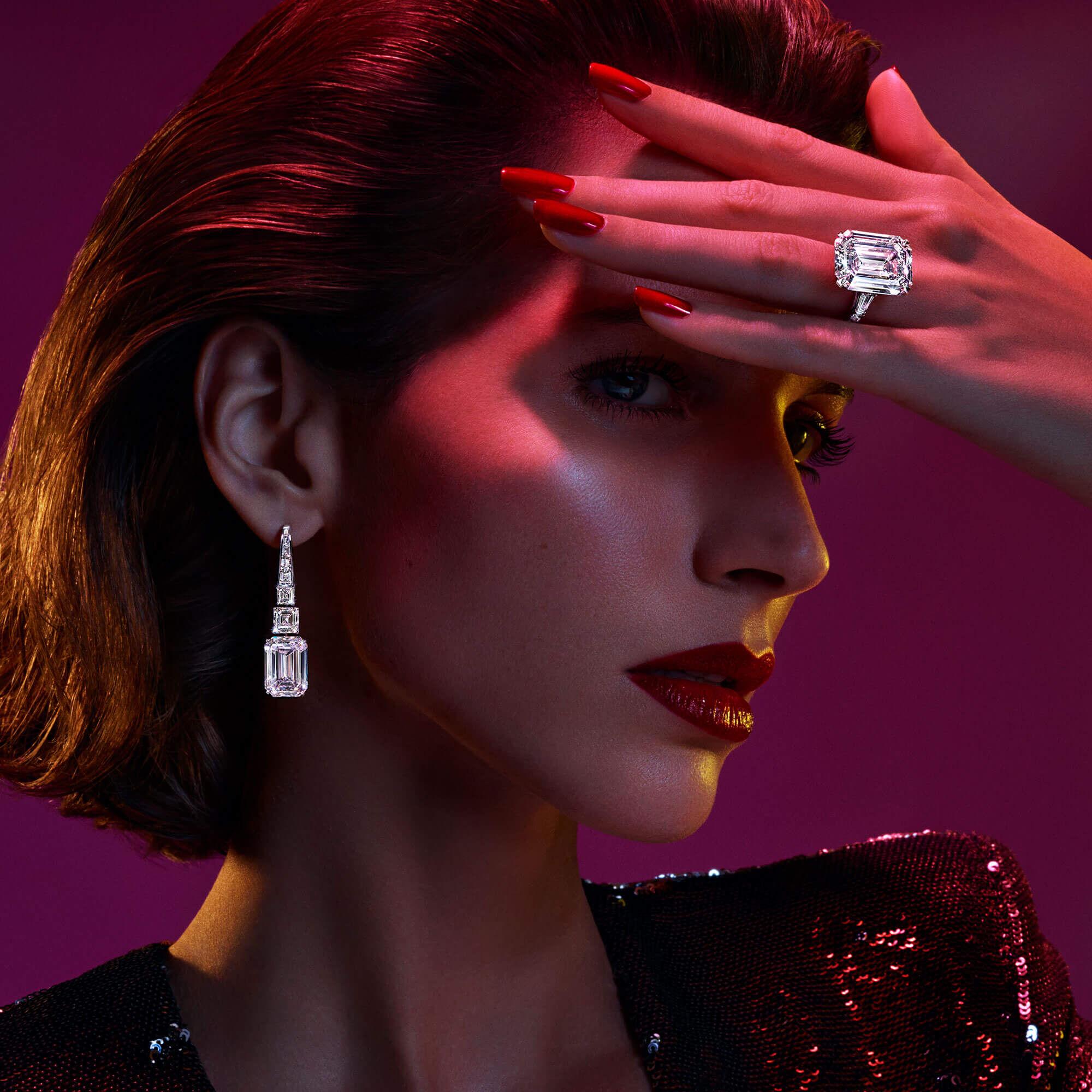 A model wears Graff high jewellery emerald cut diamond earrings and a D Flawless emerald cut diamond ring