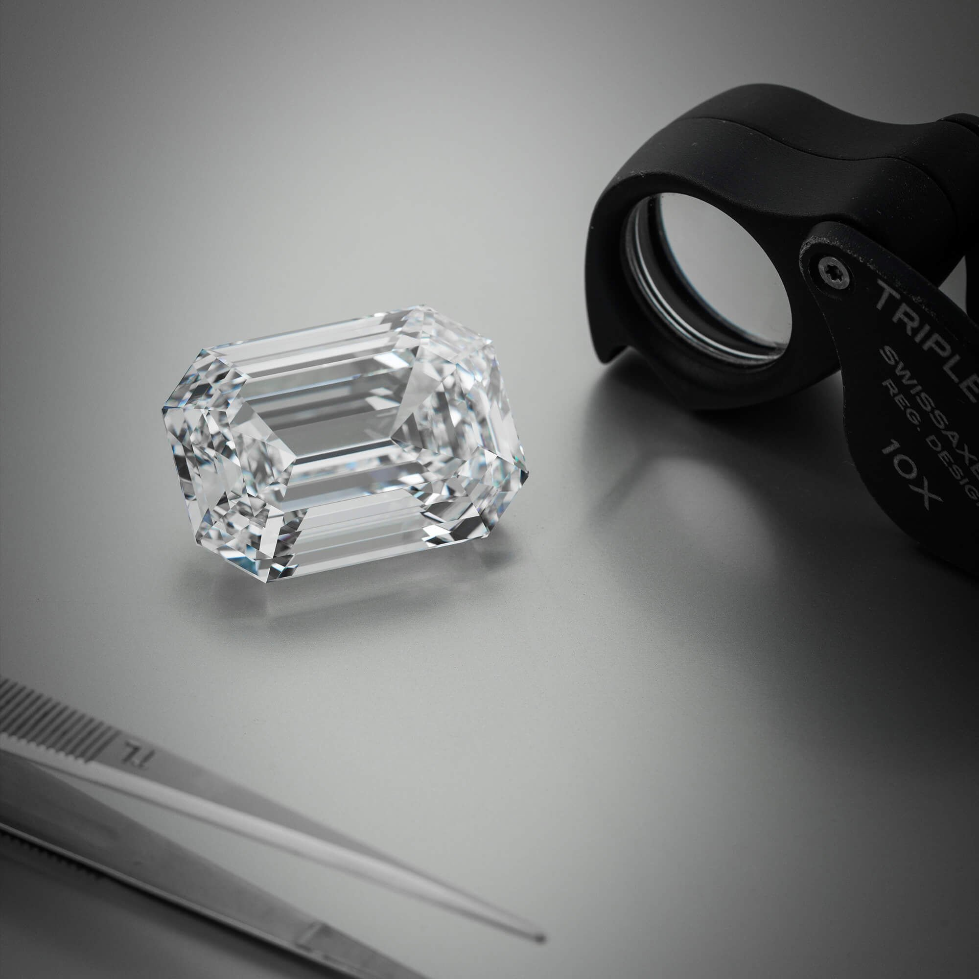 Graff Eternal Twins diamond in the workshop next to a loupe.