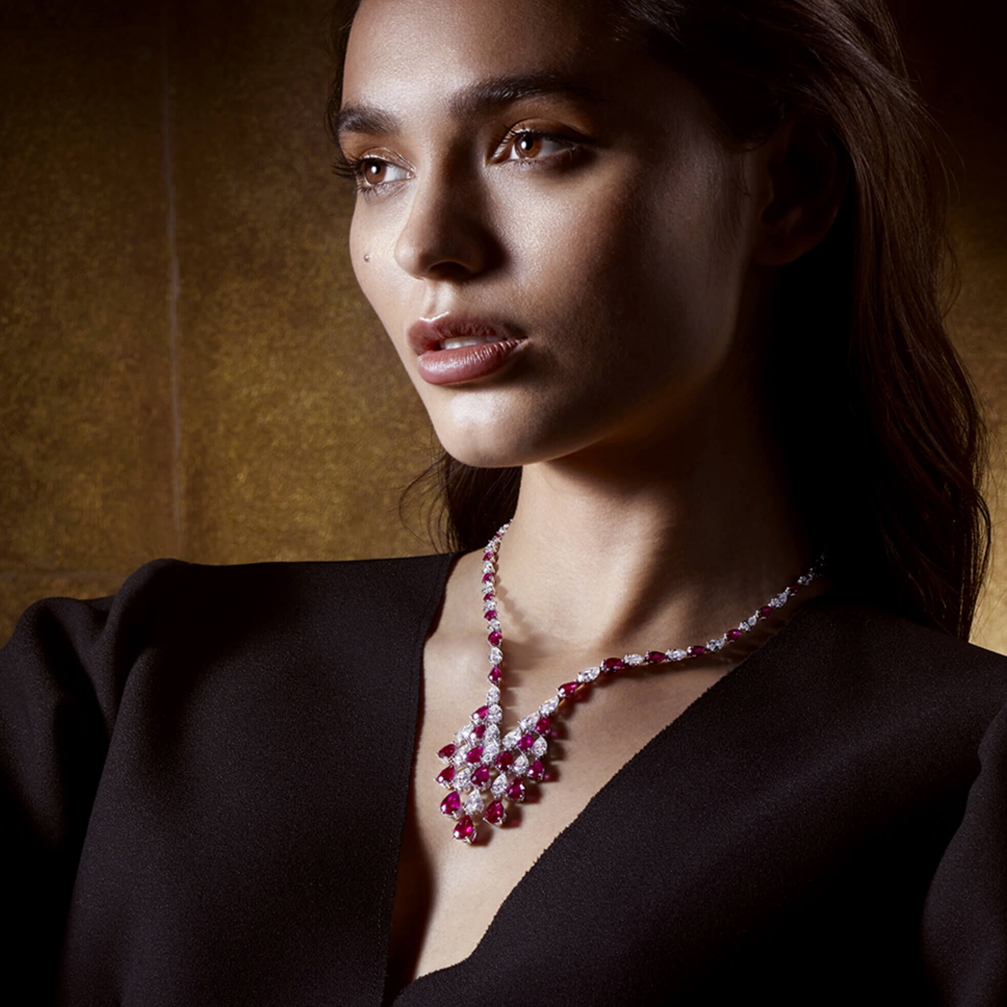 A lady wearing a Graff pear shape ruby and diamond necklace