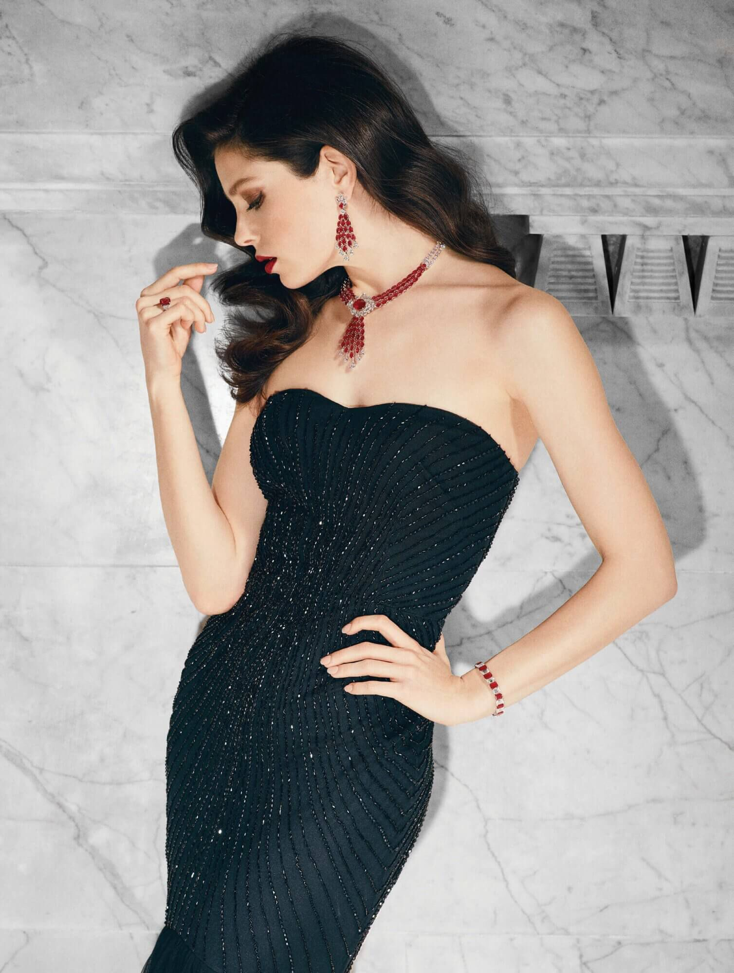 Model wears Graff Diamonds Lights Camera Action Article 6.01 carat Vivid Red oval Mozambique ruby and diamond ring Ruby and diamond earrings and Ruby and diamond necklace and bracelet