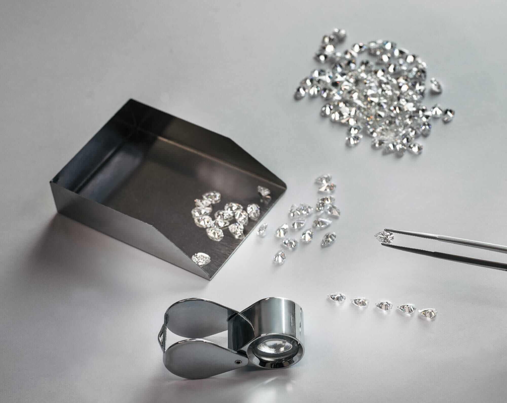 Graff diamond setter lining up diamonds with tools on the table