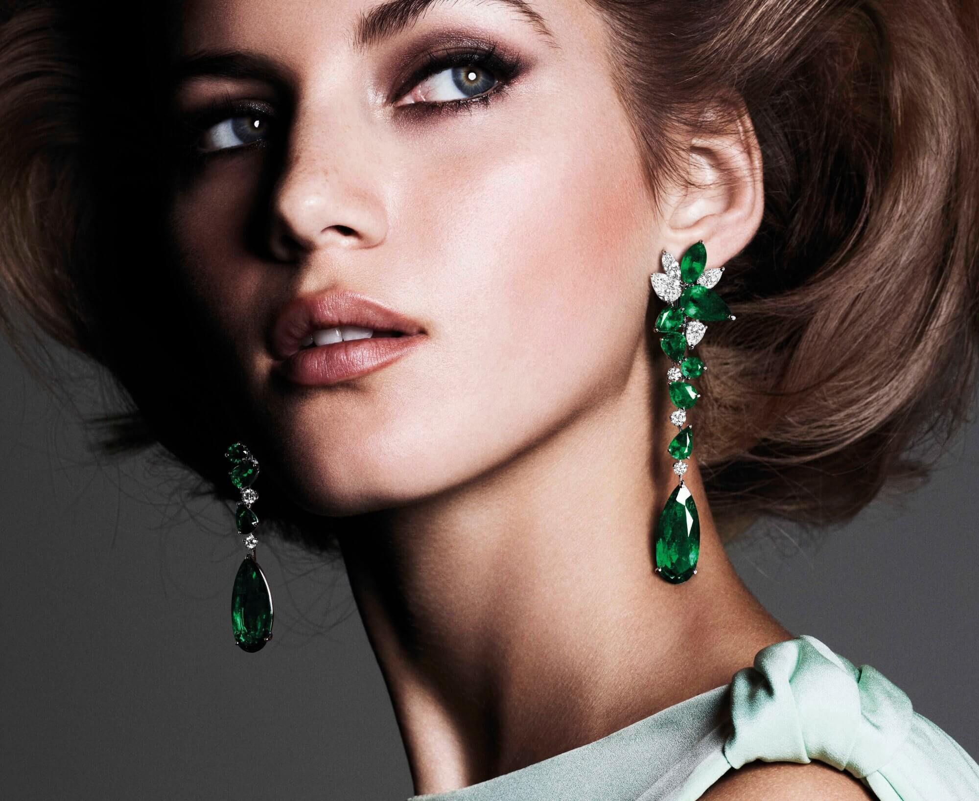 A model wearing Graff emerald and diamond earrings