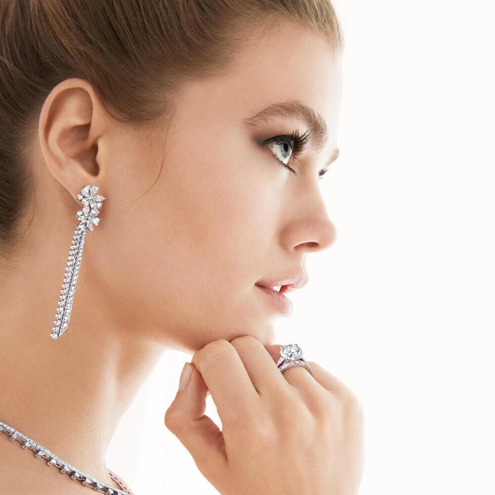 Model wears Carissa Diamond Drop Earrings, round Diamond Solitaire and Castle Set Round Diamond Wedding Band from Graff.