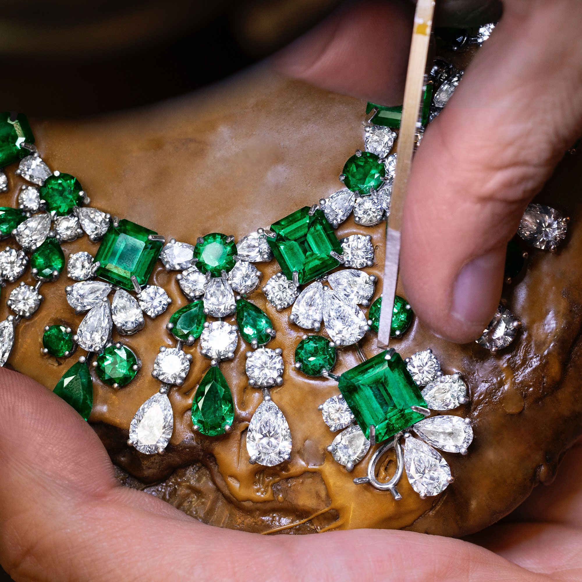 A Graff craftsman setting a emerald and diamond necklace in the workshop