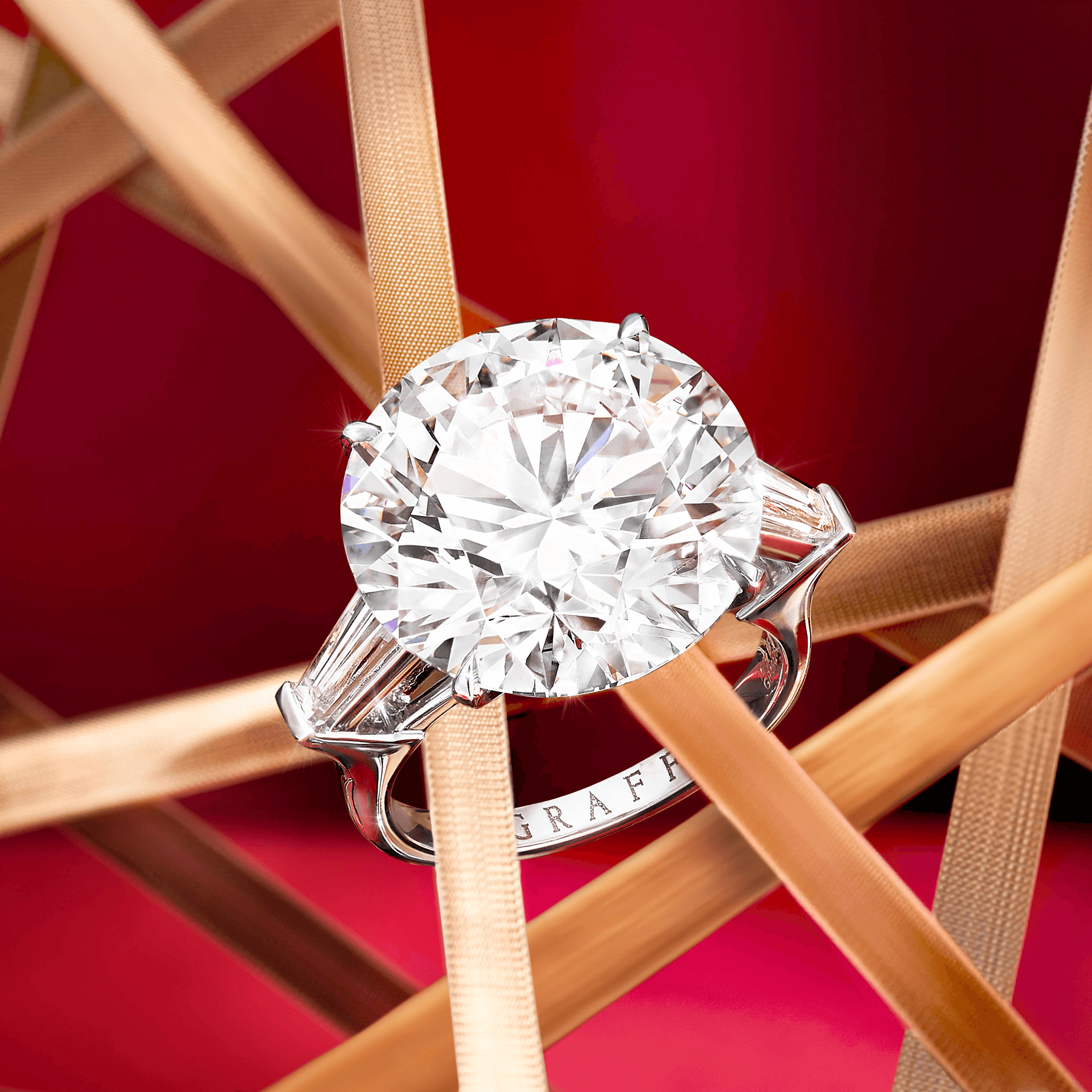 A Graff Diamond Ring featuring a round diamond with tapered baguette side stones on a red background with gold ribbons