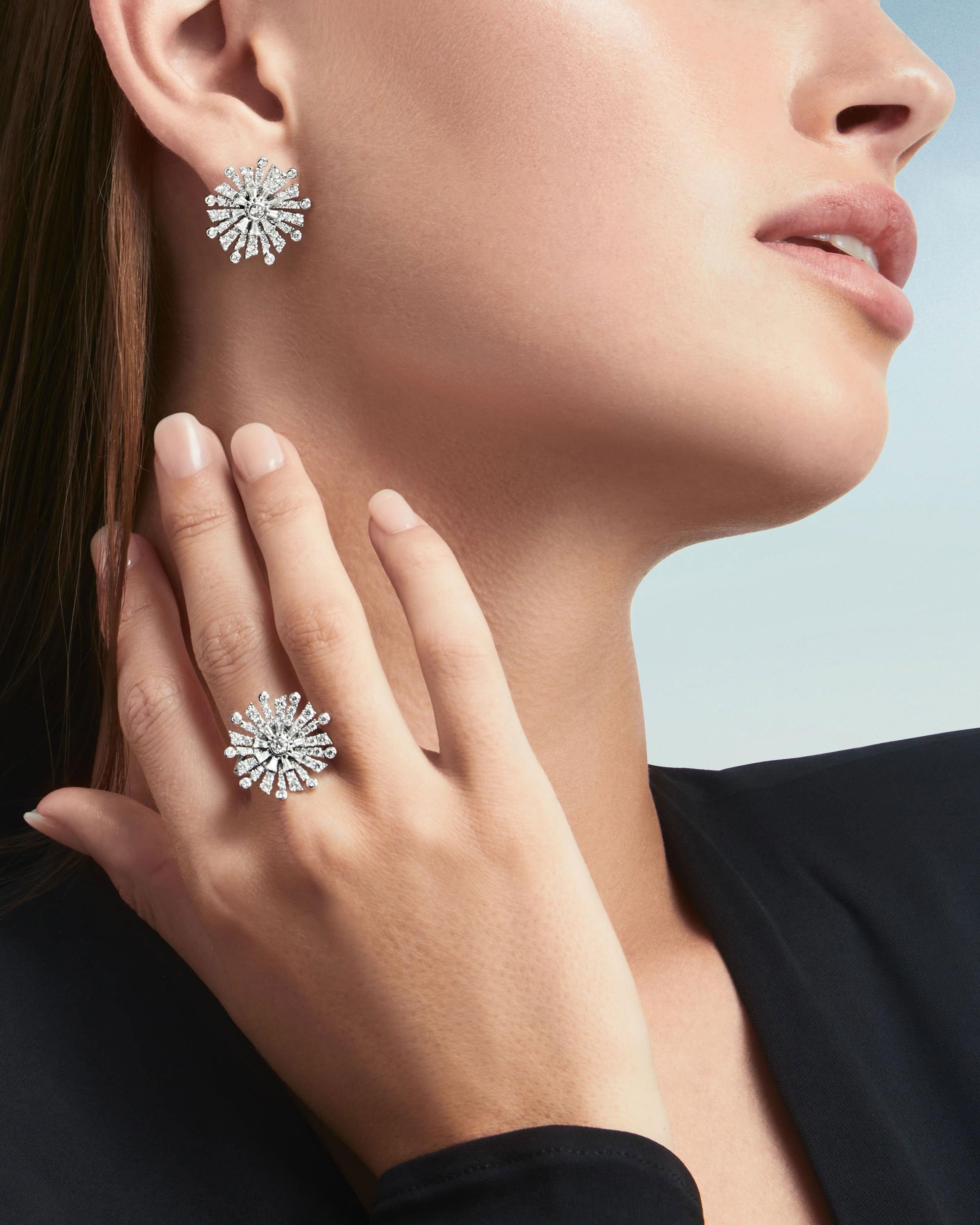 Close up of a model wearing the Graff New Dawn jewellery collection diamond earrings & ring
