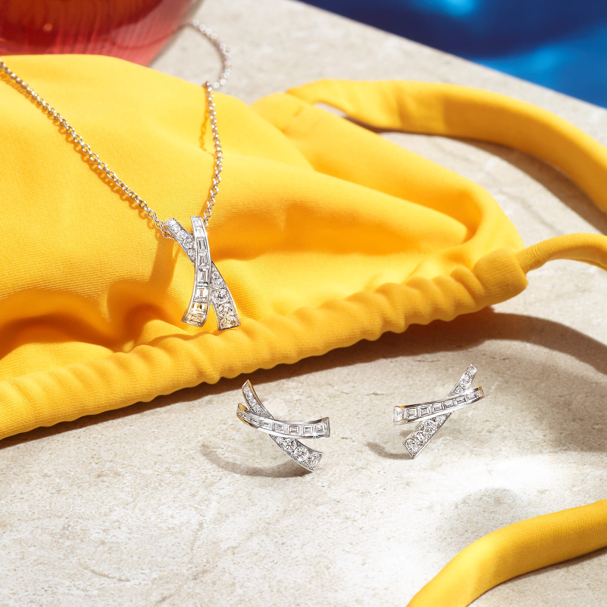Close up of the Graff Kiss collection diamond and pendant at a pool side