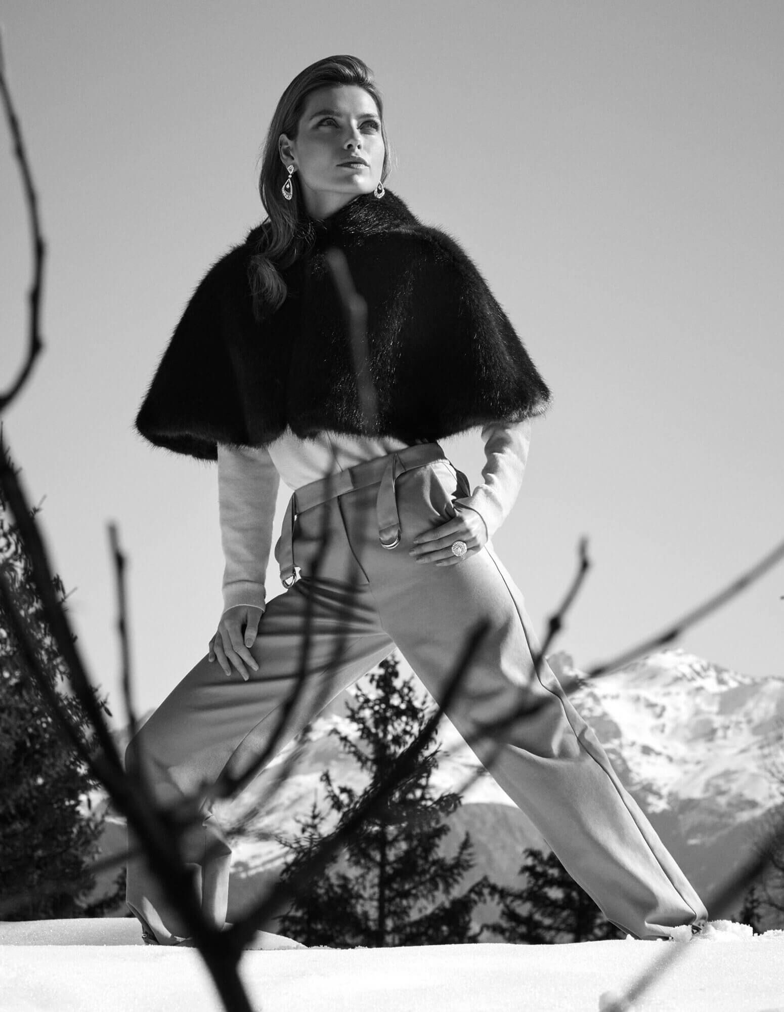 A lady on a ski slope dressed in a fur cape and wearing diamond Luna earrings and a diamond Swirl ring